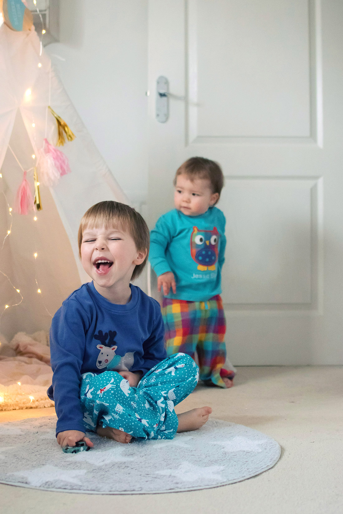 Two young brothers wearing Frugi personalised owl Slumber and reindeer pyjamas playing with fairy lights and decorating for Christmas