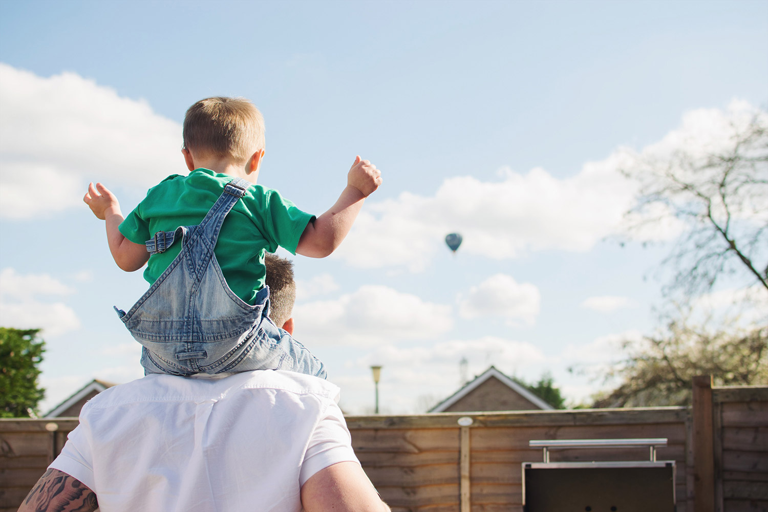 Young boy wearing Frugi t-shirt and dungarees sitting on Dad's shoulders looking at hot air balloon on Summer's Day