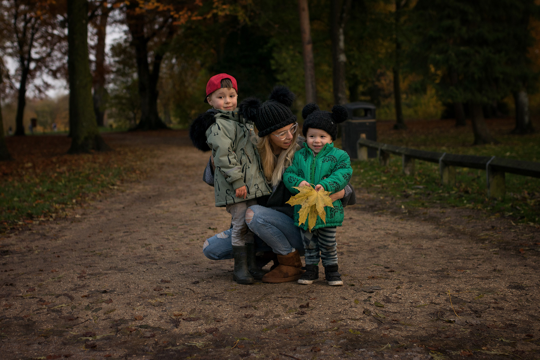Mother with two young sons, wearing Bobo Choses coat, Mini Rodini K2 penguins, picking up leaves on an Autumn walk
