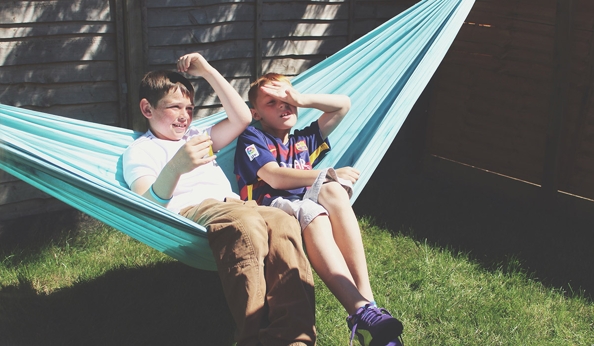 5 Steps to Pulling Off a Successful British BBQ - Cousins having fun chilling in hammock at family BBQ