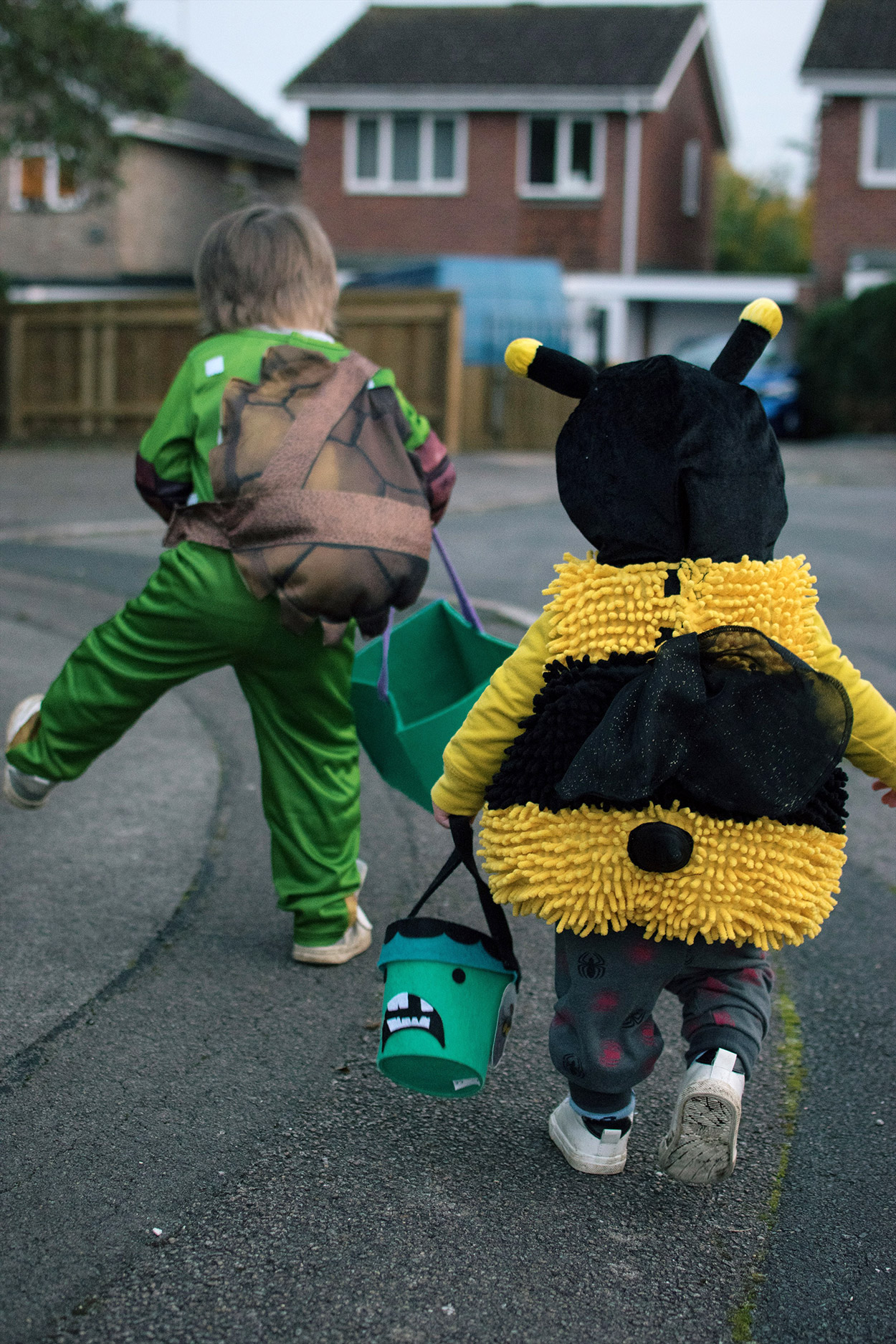 Toddler dressed in a Bumble Bee costume and pre-schooler in a teenage mutant ninja turtle Nickelodeon Leonardo outfit carrying Halloween trick or treat goodie bags visiting grandparents in in the UK