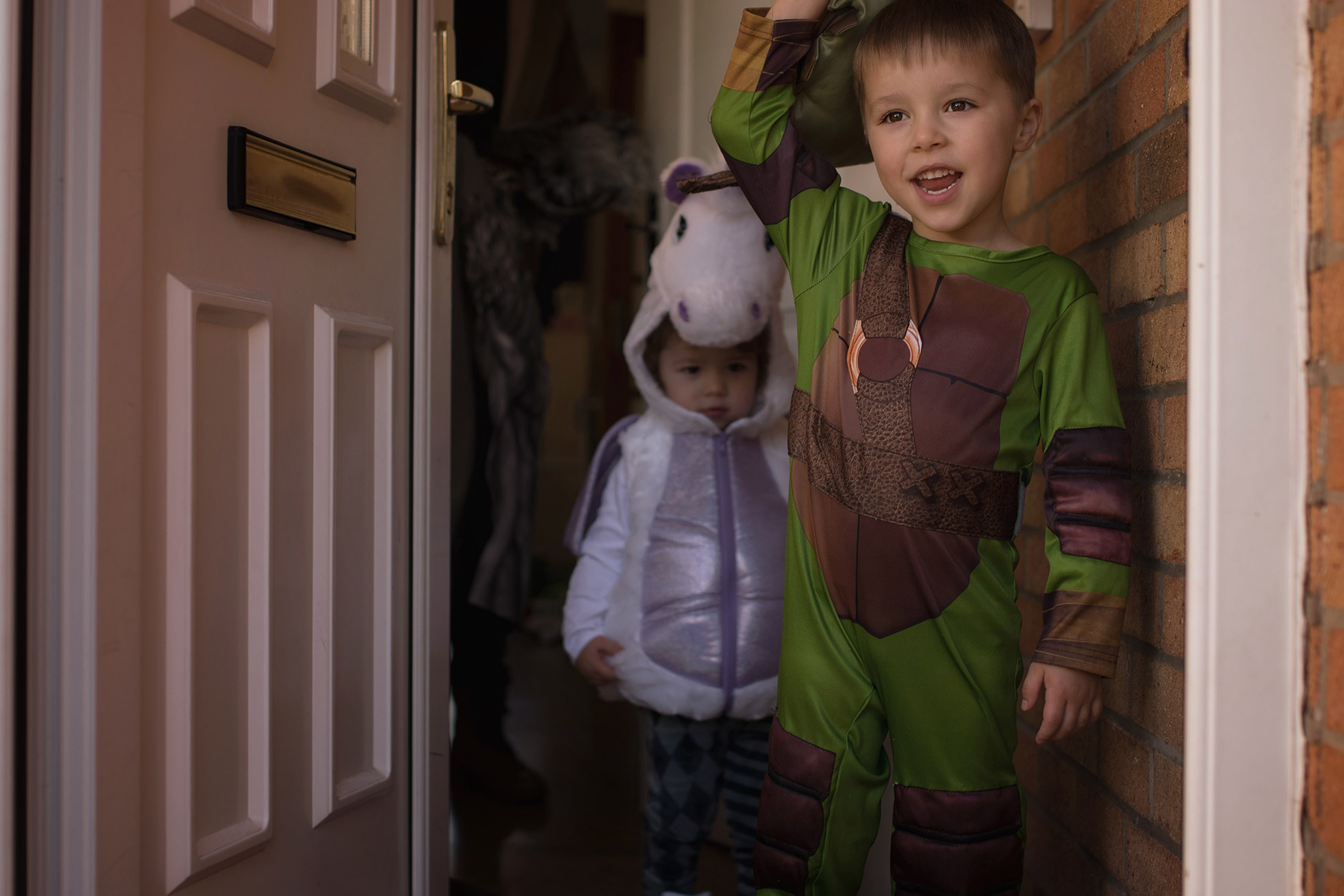 Celebrating halloween with family and boys wearing ninja turtle outfit and unicorn costume