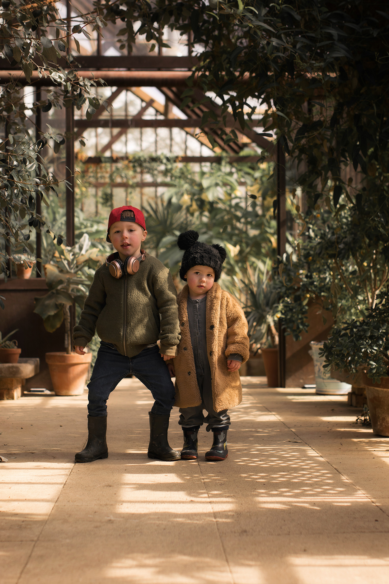 Family with two brothers exploring the gardens, ponds, newts and greenhouses at Hidcote National Trust wearing Maed for Mini and Child.ish coats