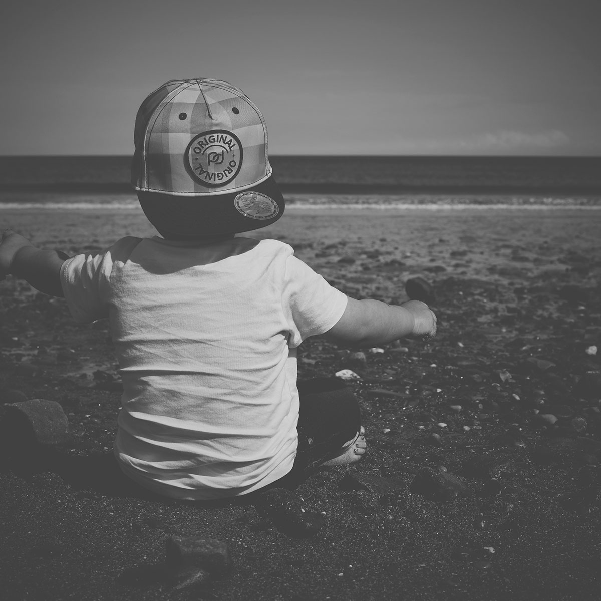 Our month in insta-snaps; May 2016 - Toddler sitting on pebble beach at the seaside wearing H&M baseball cap in South Wales, Fashion Friday
