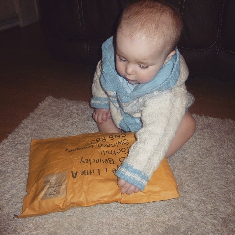 Toddler baby Archie opening up package gift envelope