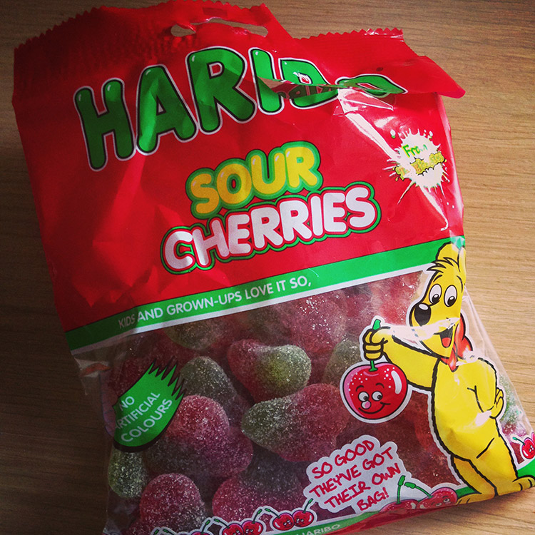 Eating Haribo sour cherry sweets candy away from baby