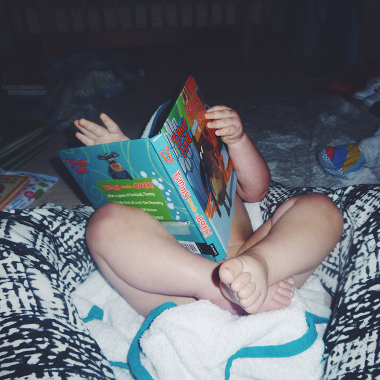 Baby toddler reading Timmy Time book before bed and bath