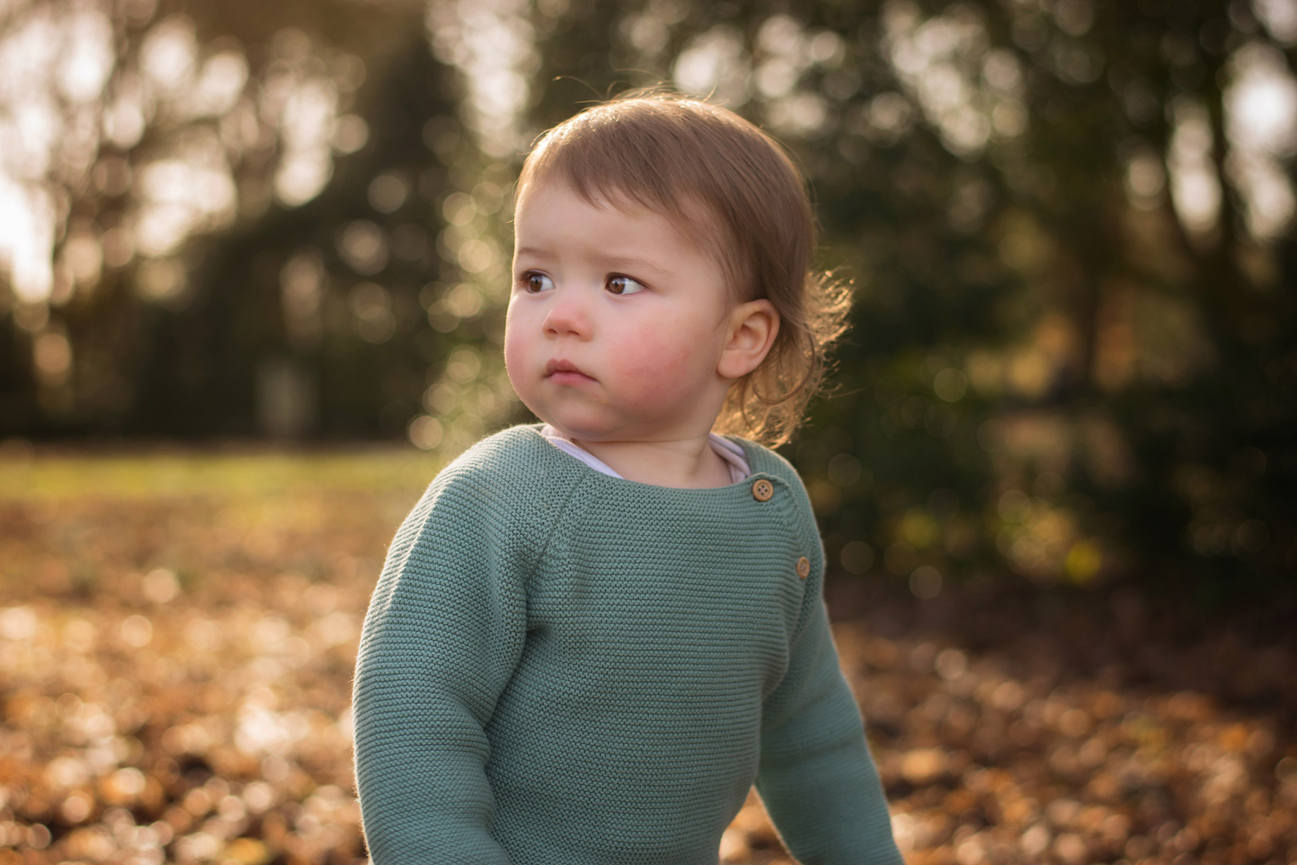 Young toddler baby boy wearing La Coqueta Darro baby jumper knitwear on woodland walk with Mother amongst the snowdrops