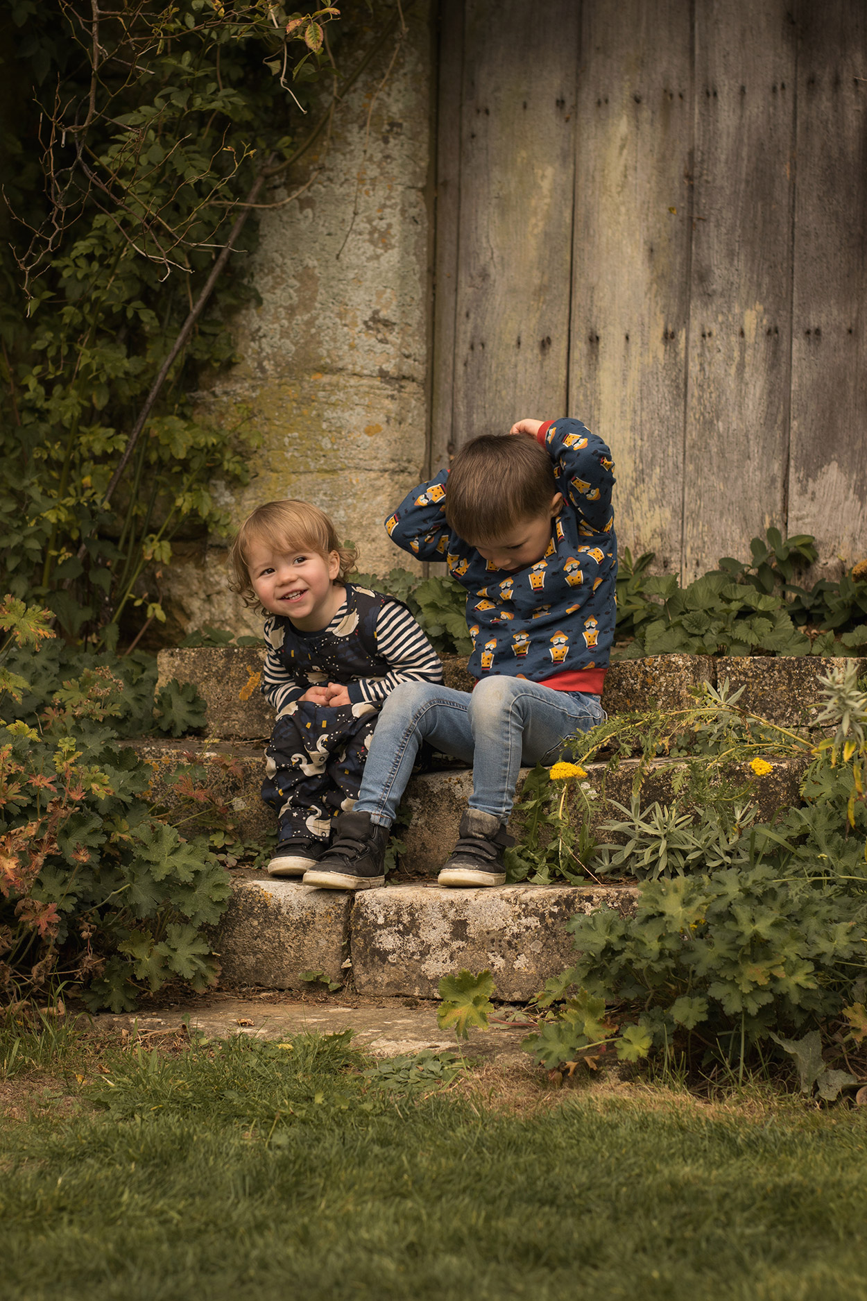 Young boy and toddler brother wearing Little Green Radical swan dungarees and night fisherman sweatshirt playing at Chastleton House, Oxfordshire