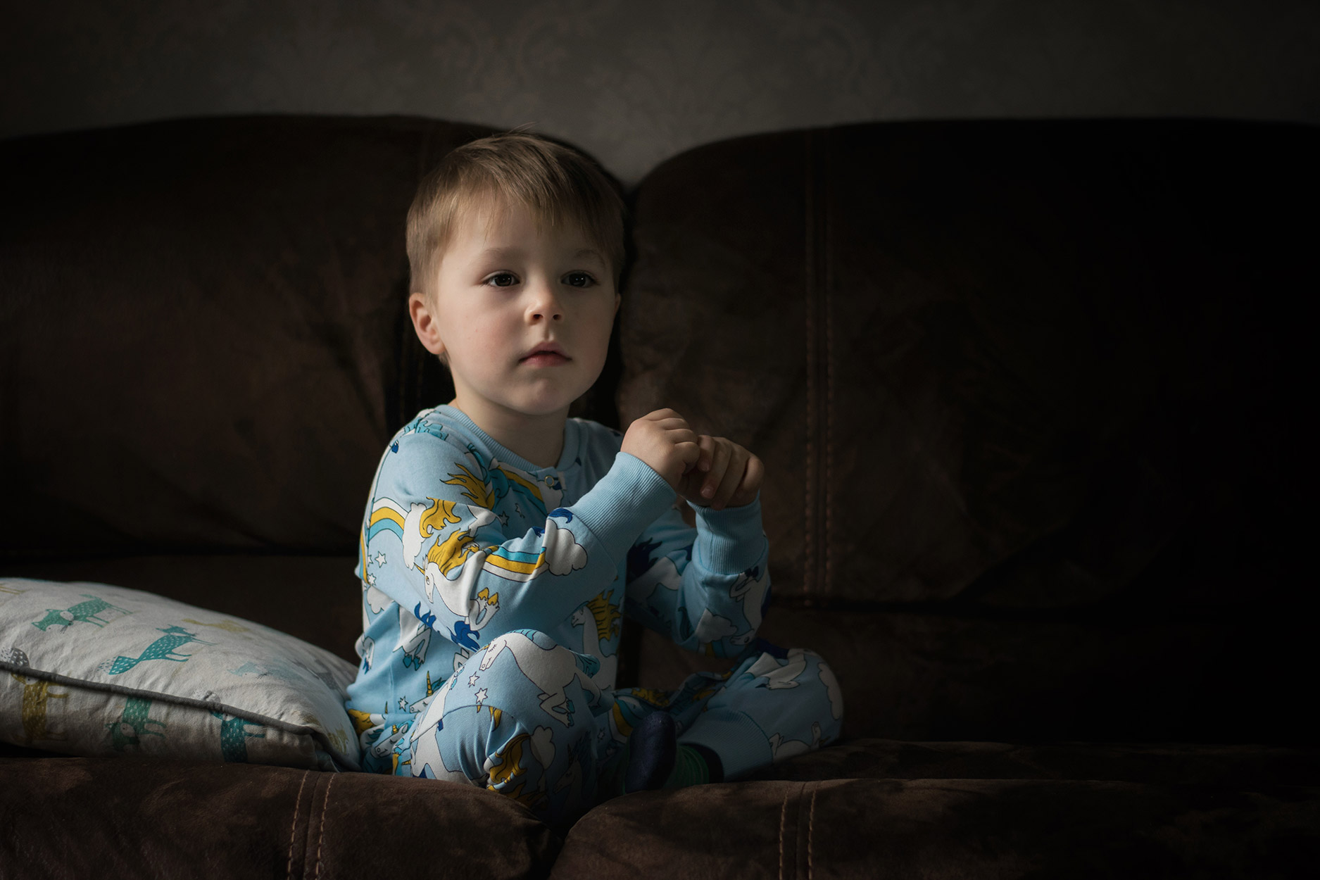 Young boy wearing Mini Rodini unicorn blue onesie sitting on sofa next to large window for portrait shot