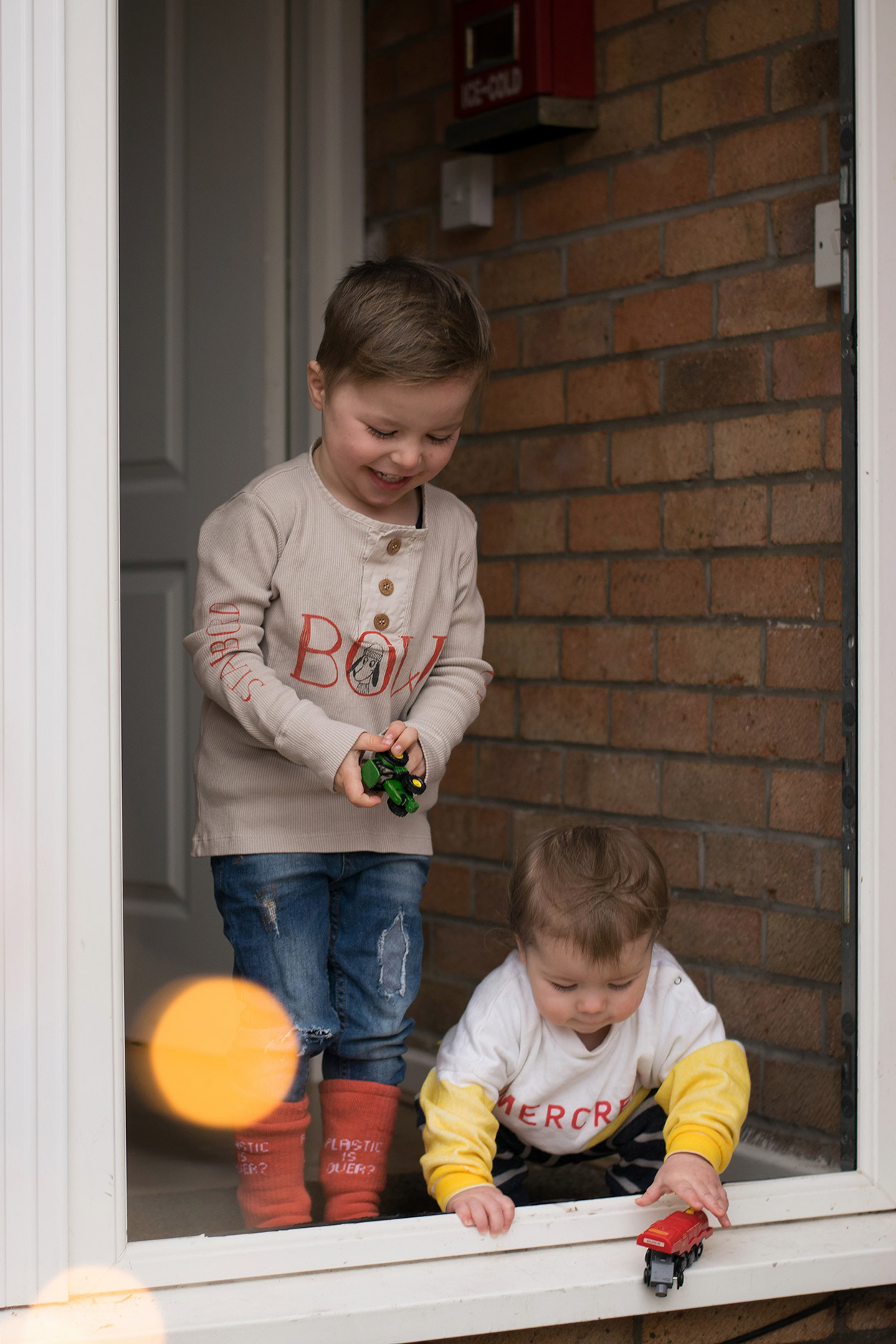 Two young brothers playing with cars at the front of terraced house, wearing Bobo Choses AW17 clothing