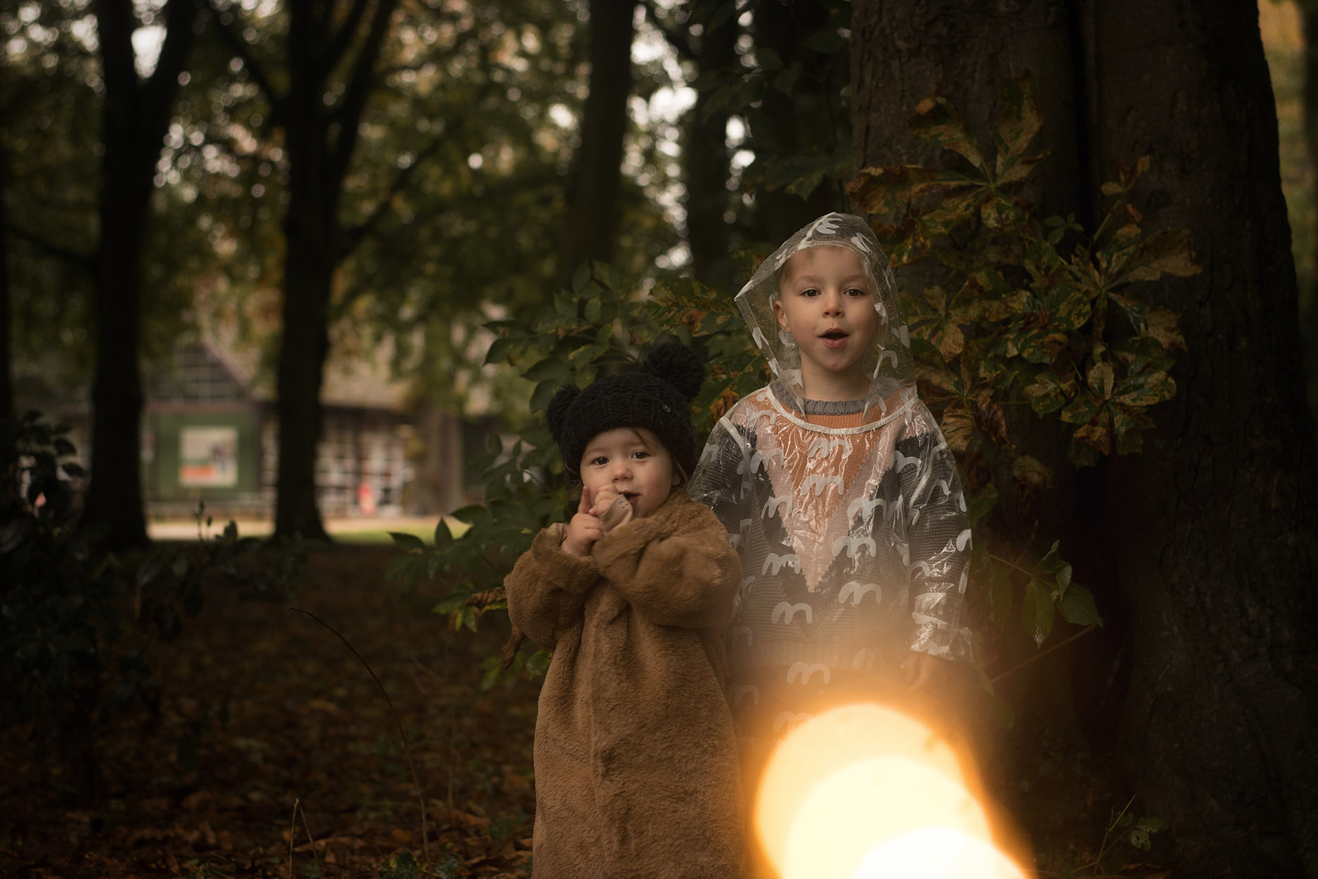 Toddler wearing Maed for Mini fur coat, MyK by Myleene black knit hat with brother wearing Bobo Choses rain mac and Iglo + Indi jumper in woodland for the onset of the Autumn season