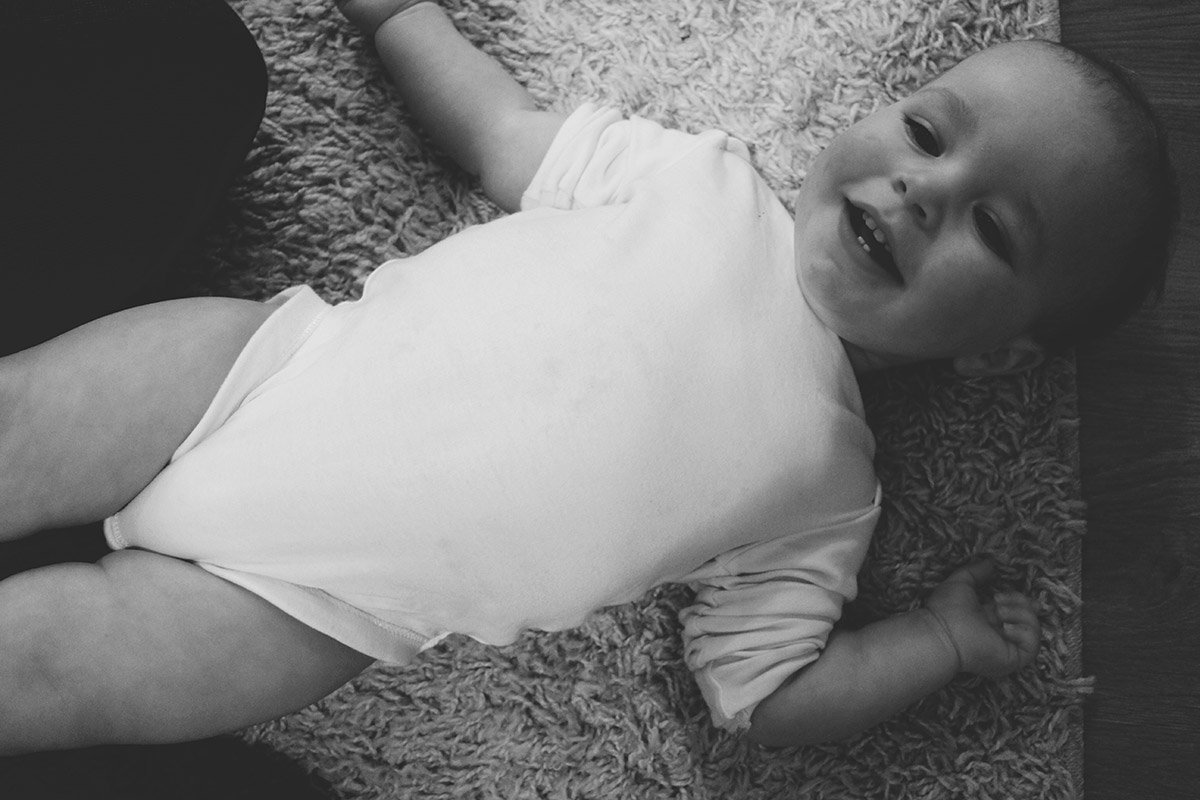 14 month old toddler laying down wearing white vest smiling
