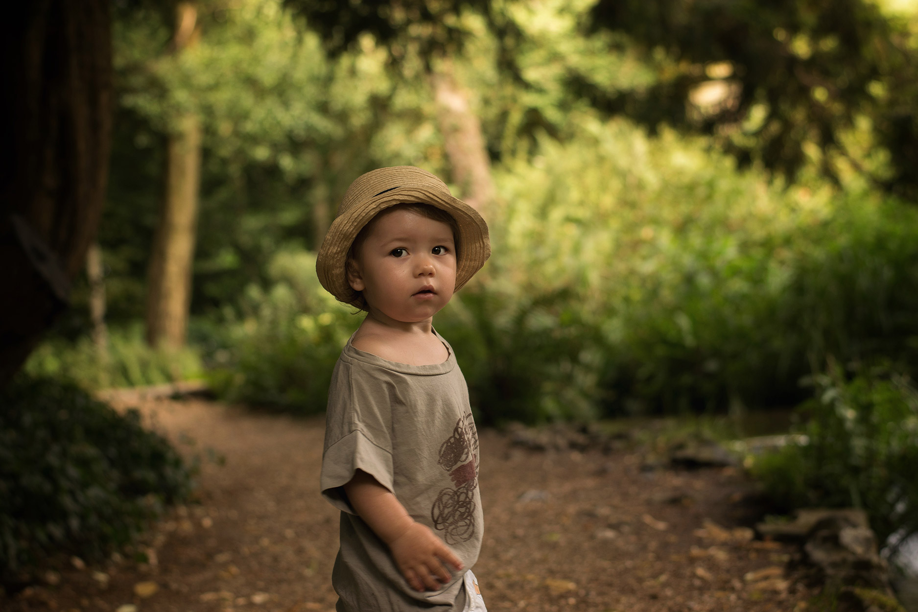 Young toddler boy wearing Bobo Choses JOHN t-shirt and trilby straw hat visiting National Trust property Mottisfont House and gardens, Hampshire
