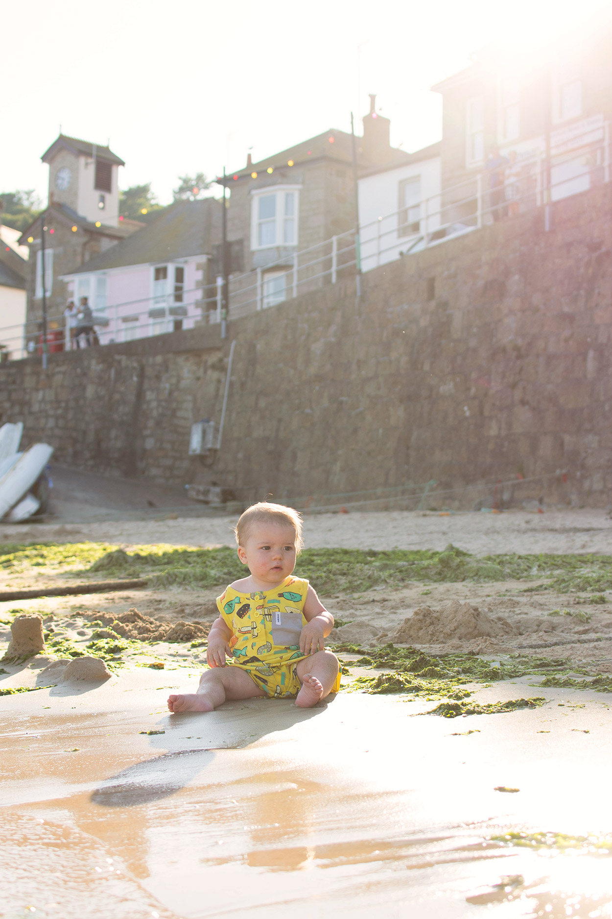 Two brothers, aged 1 and 3 wearing Indikidual sushi playsuits and playing on the harbour beach, splashing in the sea in Mousehole, near Penzance, Aspects Holidays