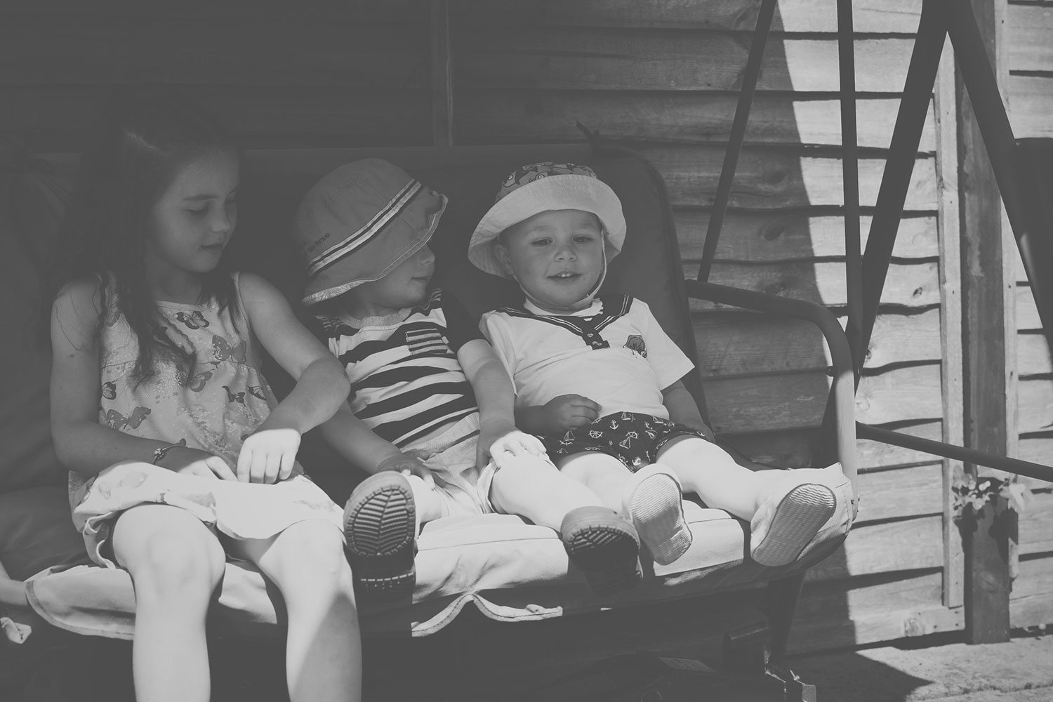 'A cousin is a little bit of childhood that can never be lost' — The Ordinary Moments #9; Cousins sitting together on the garden swing at a family Summer BBQ