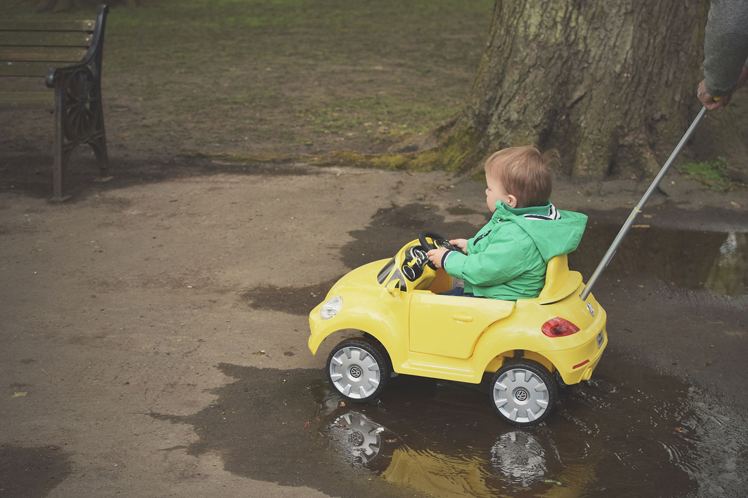 Grandparents sort of sprinkle stardust over the lives of their grandchildren — The Ordinary Moments #8; Toddler playing in the park wearing green Next raincoat in yellow toy mini ride-on car