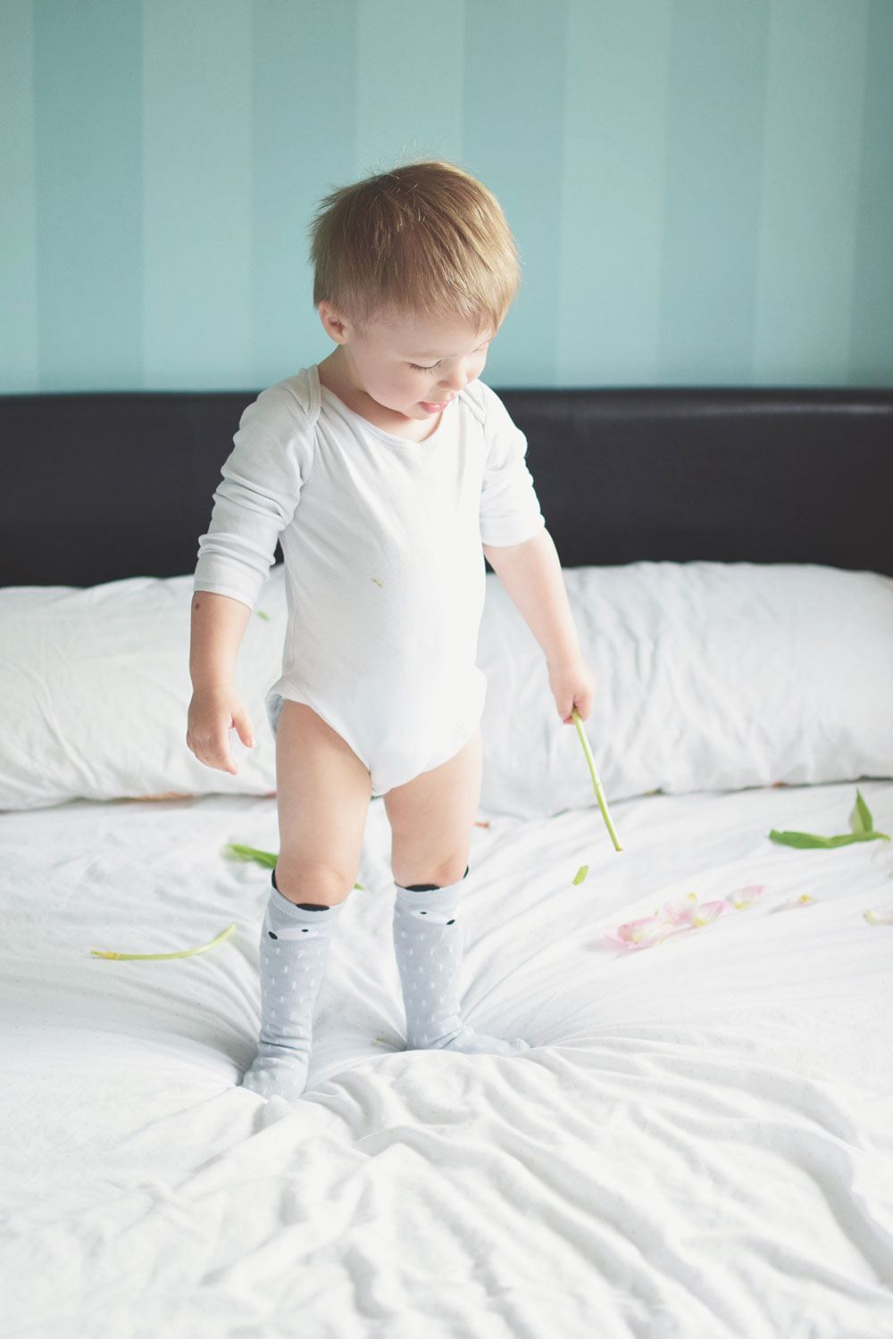Dear A, Today was one of the hardest days.. — The Ordinary Moments #7; Toddler wearing long grey fox socks and white vest jumping on the bed with pink tulips taken with Nikon D3300