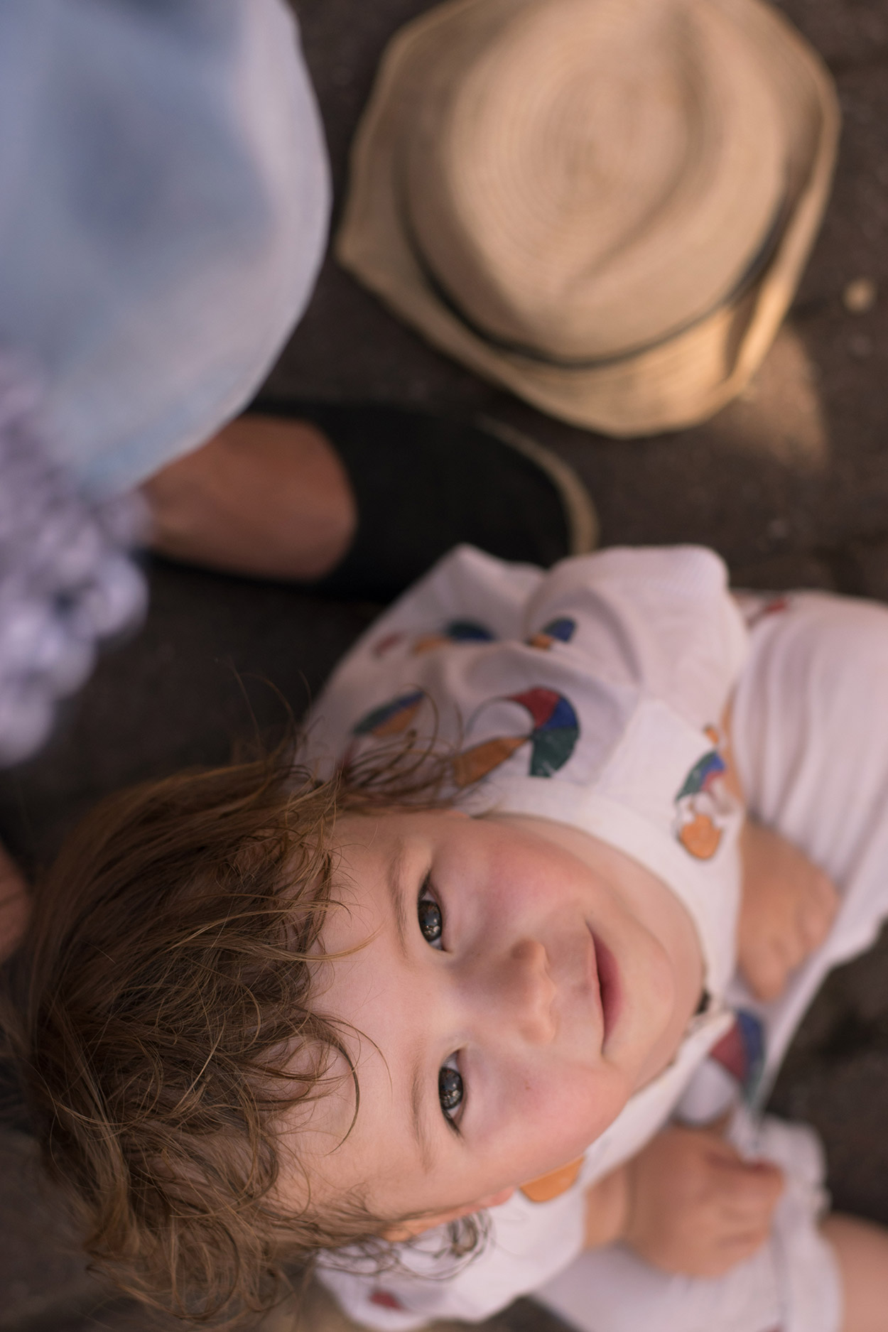 Toddler looking up at the camera wearing Bobo Choses beach balls romper - A family day out to Peppa Pig World and the Lost Kingdom at Paultons Park, Hampshire