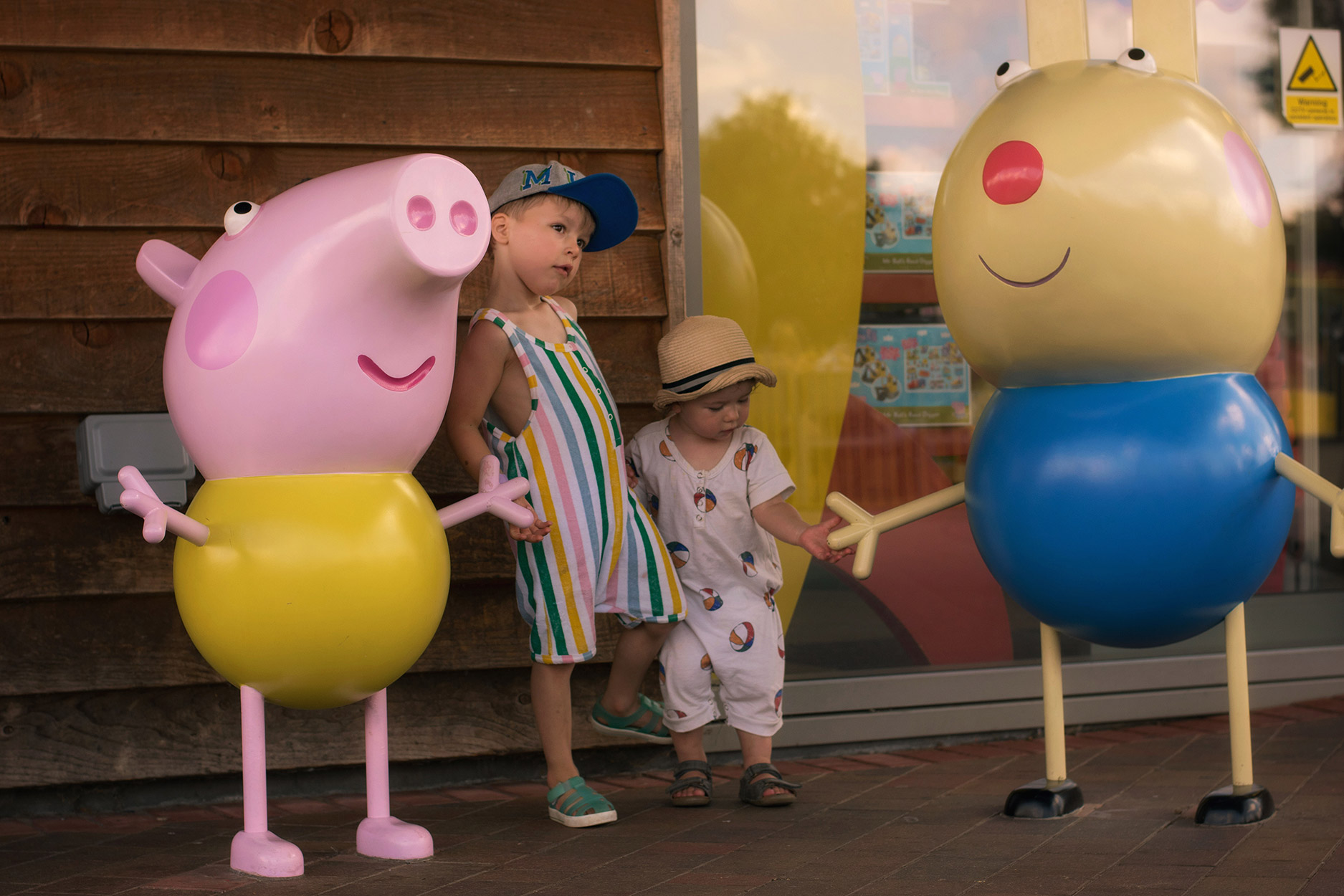 Two brothers wearing Hugo Loves Tiki striped romper and Bobo Choses with Peppa models - A family day out to Peppa Pig World and the Lost Kingdom at Paultons Park, Hampshire