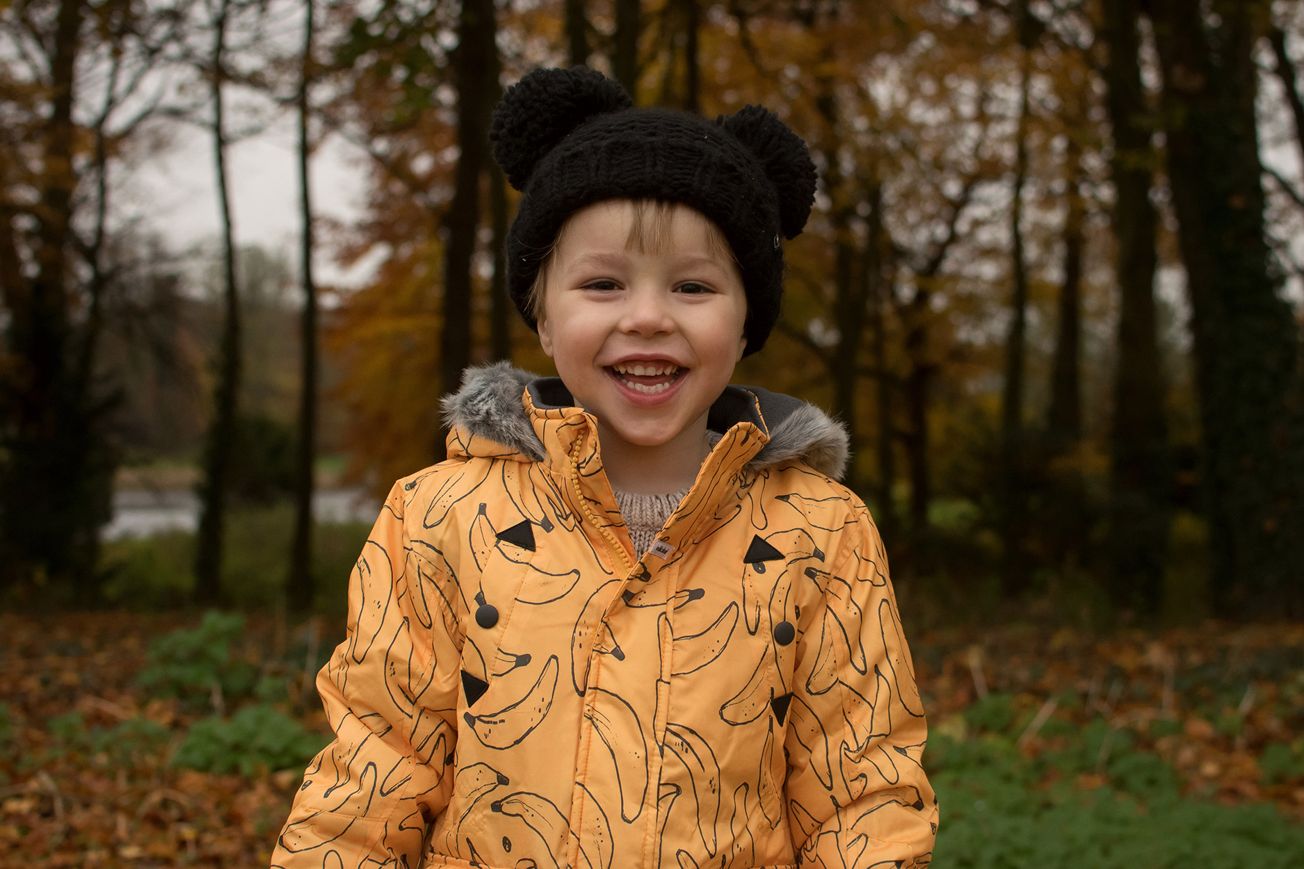 Pre-schooler wearing a banana Individual coat and MyK by Myleene Klass black bobble hat smiling at the park - taken on a Nikon D3300 with 35mm lens