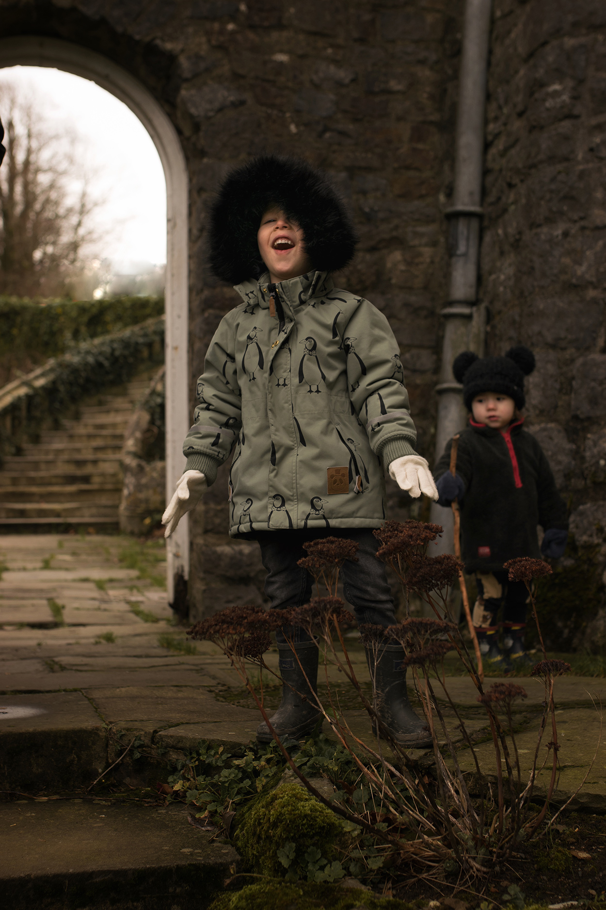 Family of four with two young brothers wearing Mini Rodini penguins and Joules wellies and fleece expiring the grounds of Picton Castle, Pembrokeshire