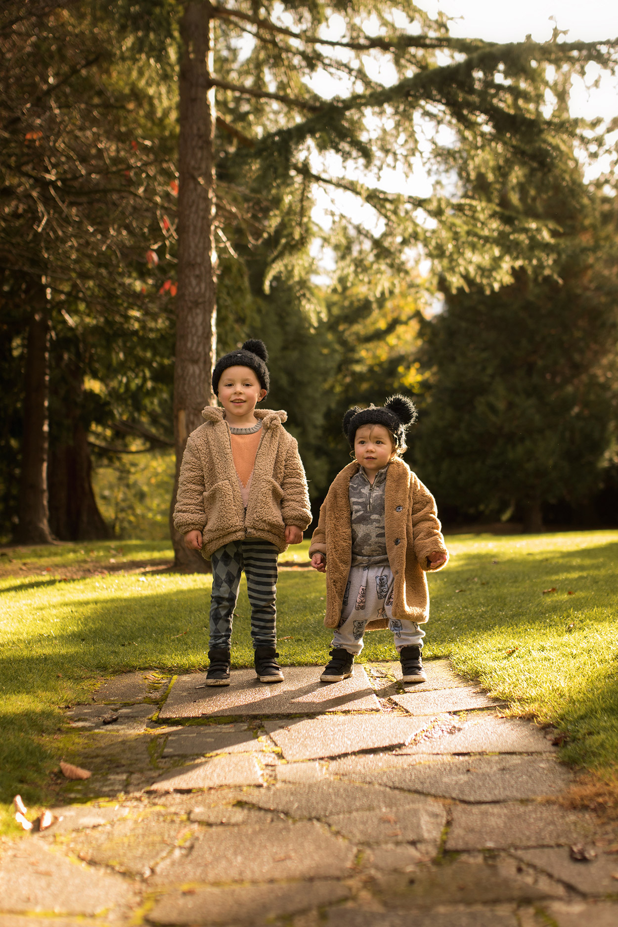 Two brothers wearing Rylee and Cru faux fur coat, Maed for Mini, Iglo and Indi jumper and Hugo Loves Tiki gummy bear romper racing around the park on an Autumn walk