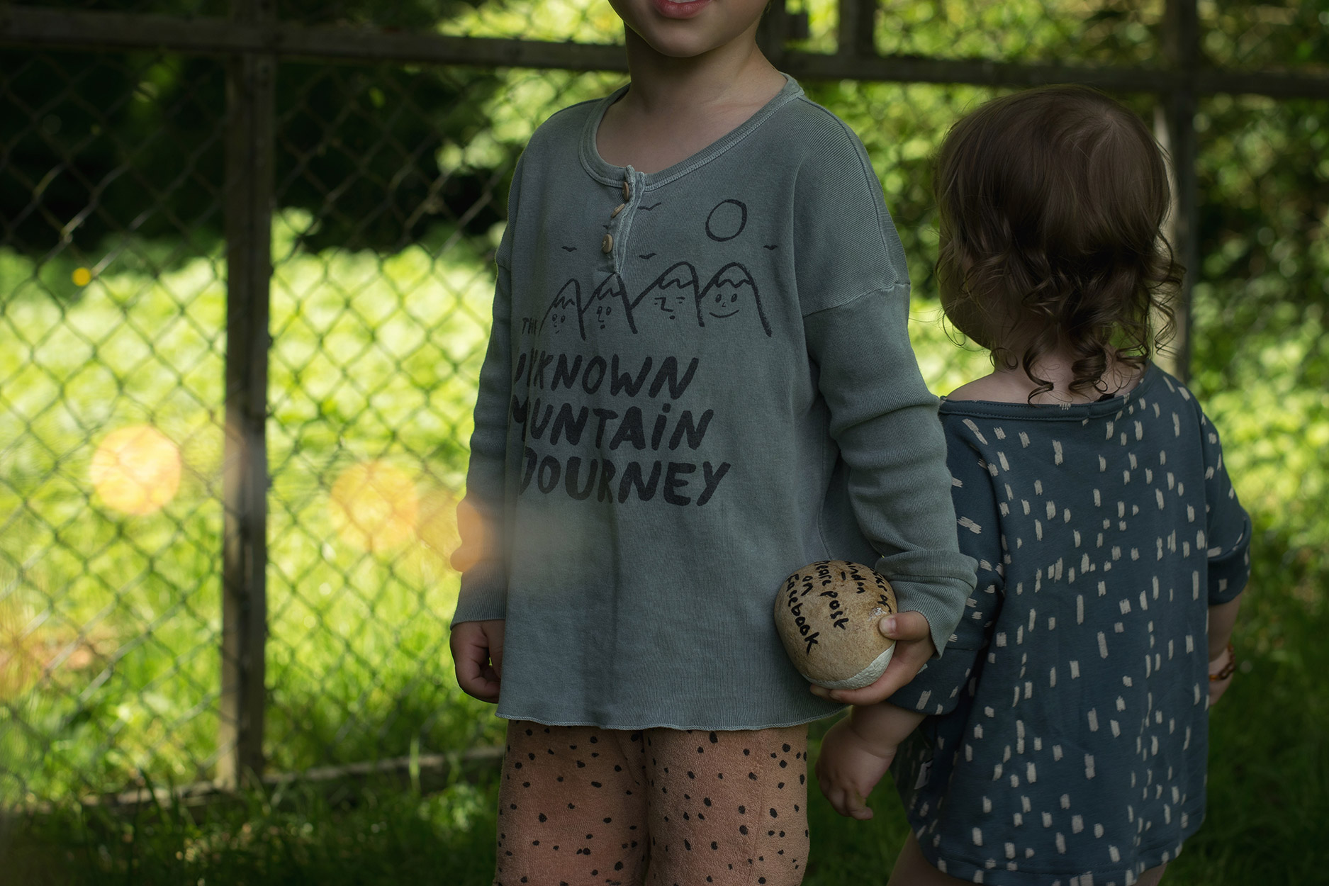 Two young boys wearing Bobo Choses 'The Unknown Mountain Journey' top, Made for Mini spotted shorts and Mr Wolf kids Luna top searching for painted rocks at Stanton Park, Wiltshire
