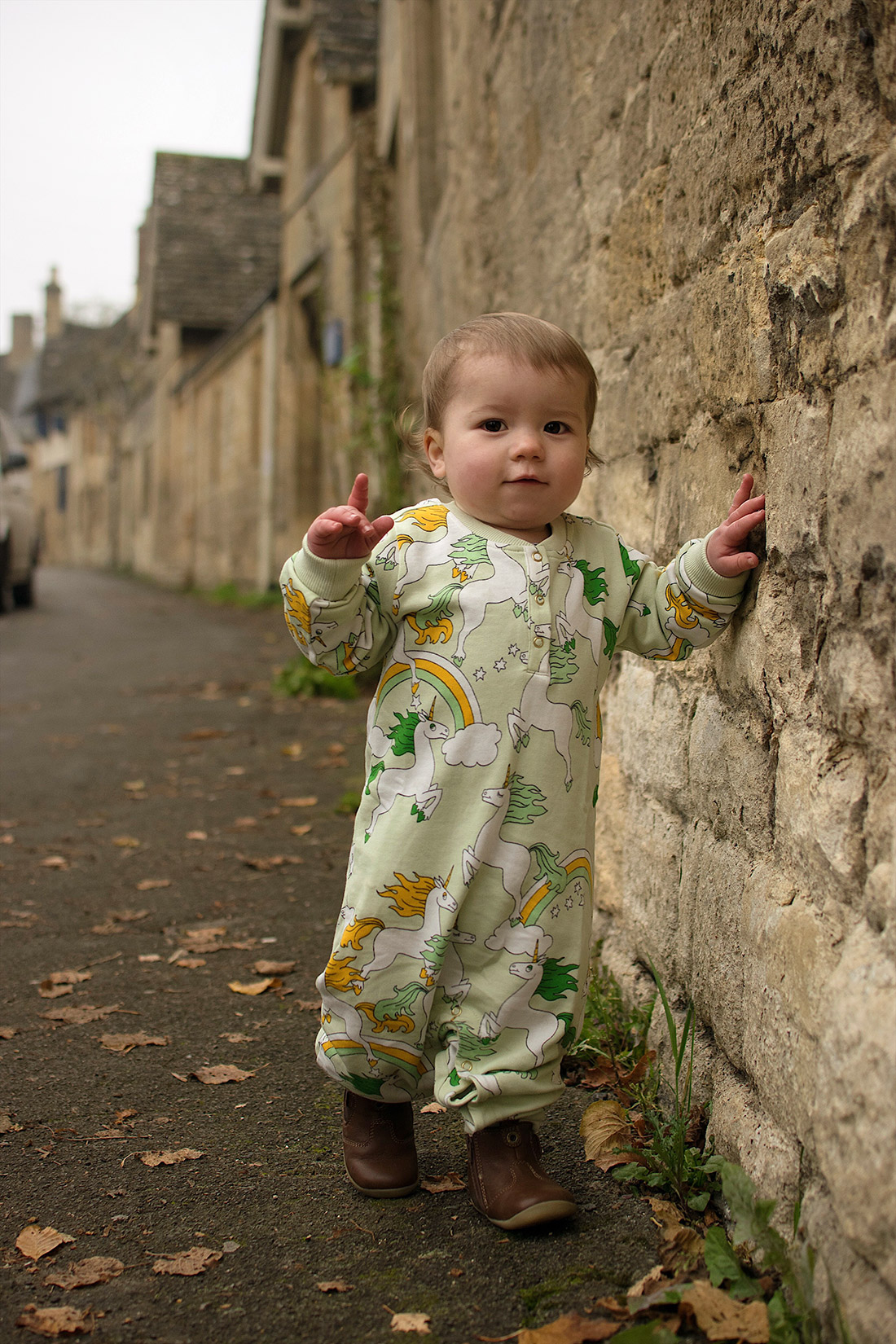 Mother holding pre-schooler son wearing My K hat, Frugi snuggle fleece, Mini Rodini unicorn leggings and Bobux shoes in Burford, Cotswolds, high street looking at village houses
