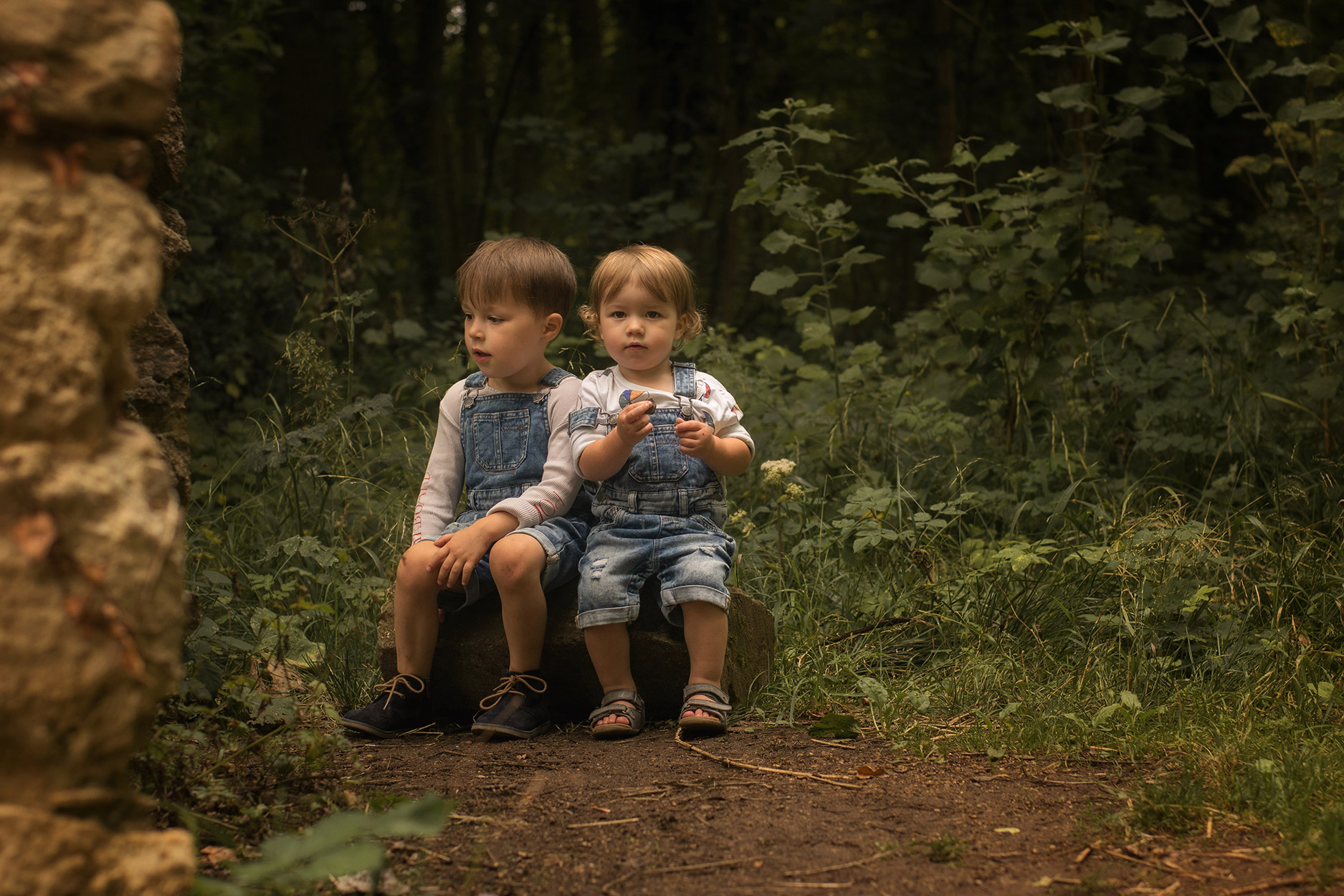 Two young brothers at the woodlands wearing Bobo Choses balls t-shirt, BOW top, Next denim dungarees, Bobux driftwood sandals and George boots