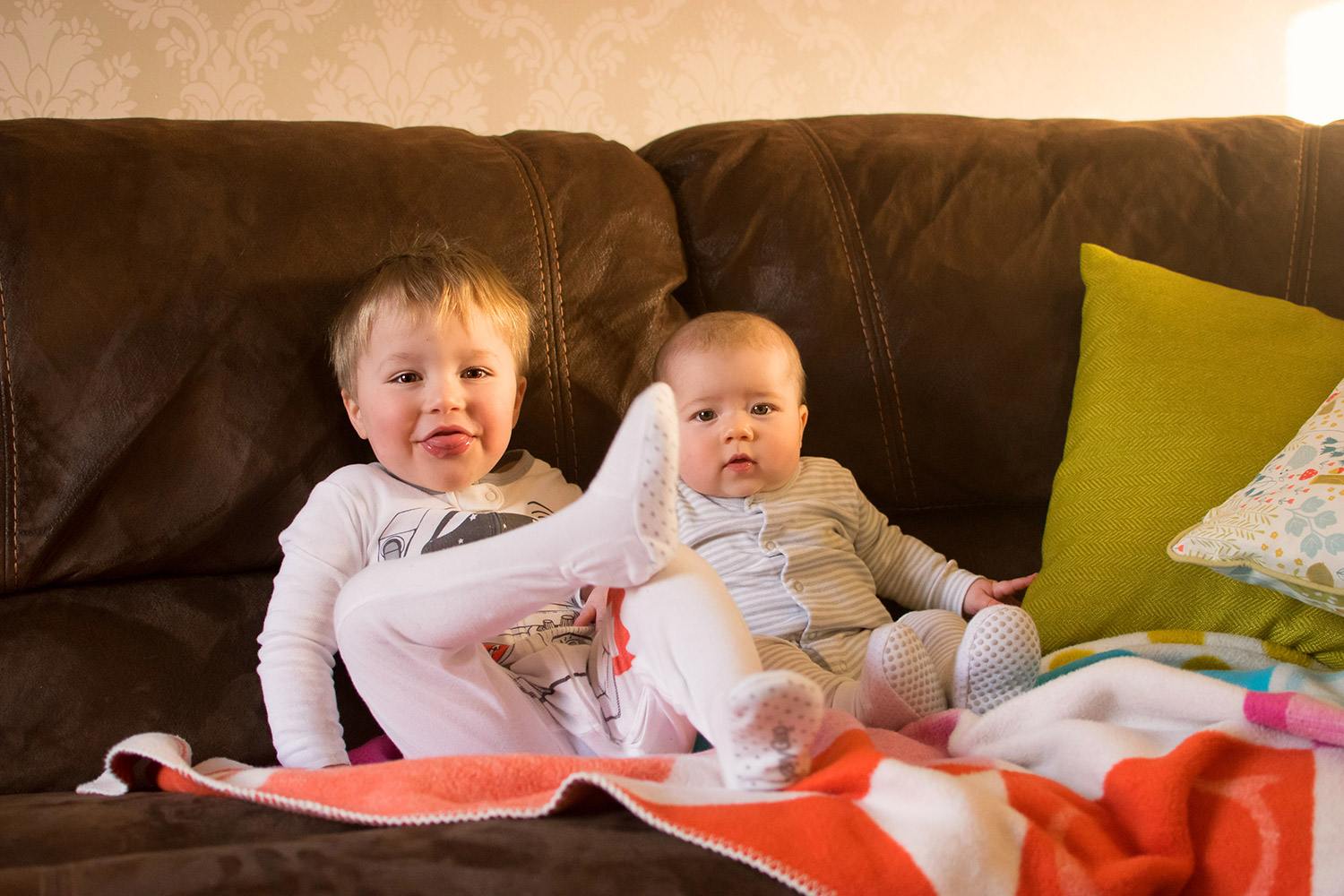 The Siblings Project {February 2017} - 6 month old baby boy with his pre-school toddler 3 year old brother cuddling together on the sofa wearing Gap astronaut onesie and George striped sleepsuit smiling in sunny glow for the siblings project