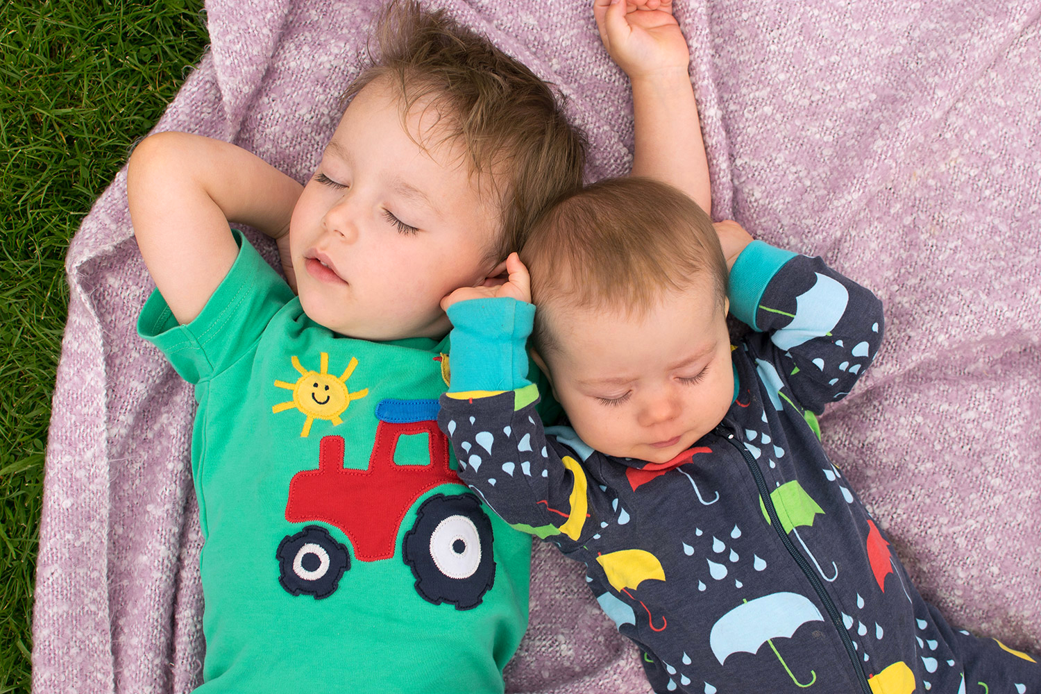 Siblings   July 2017 - 3 year old and 10 month old baby brothers and siblings wearing Frugi green tractor t-shirt and Duns Sweden umbrella print onesie sleeping on a blanket at a picnic outside on a Summer's day