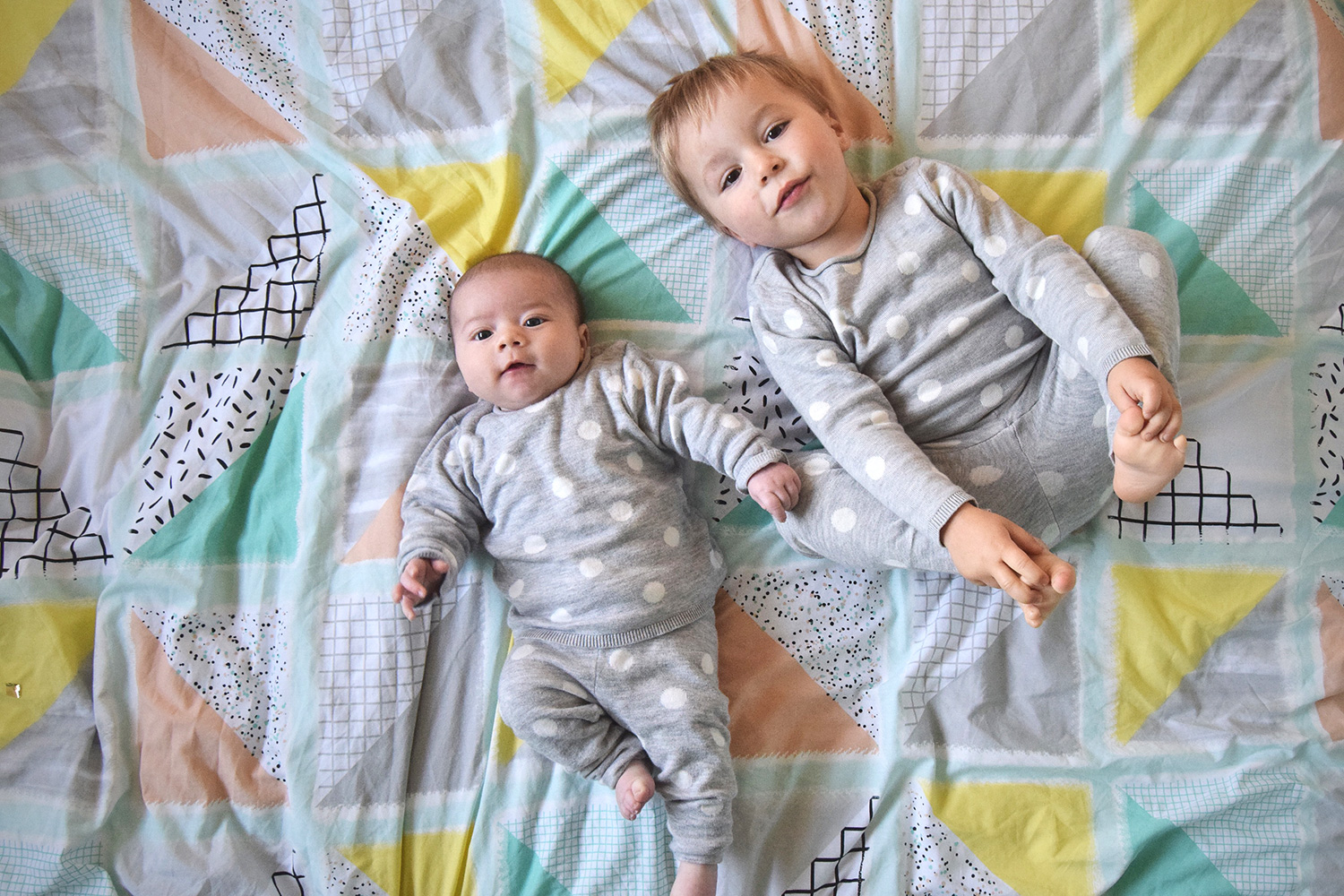 The Siblings Project {November 2016} - Newborn baby and toddler brothers wearing matching twinning H&M spotty outfits laying on Primark geometric duvet bedspread in the siblings project