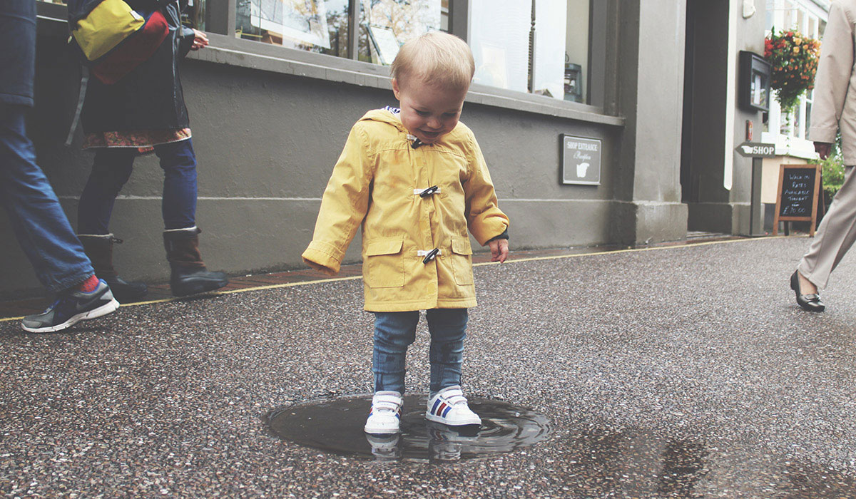 10 Things That Will Undoubtedly Happen on Your Family Staycation - Toddler wearing George yellow rain mac splashing in puddles at Lynton & Lynmouth in the rain, by the seaside