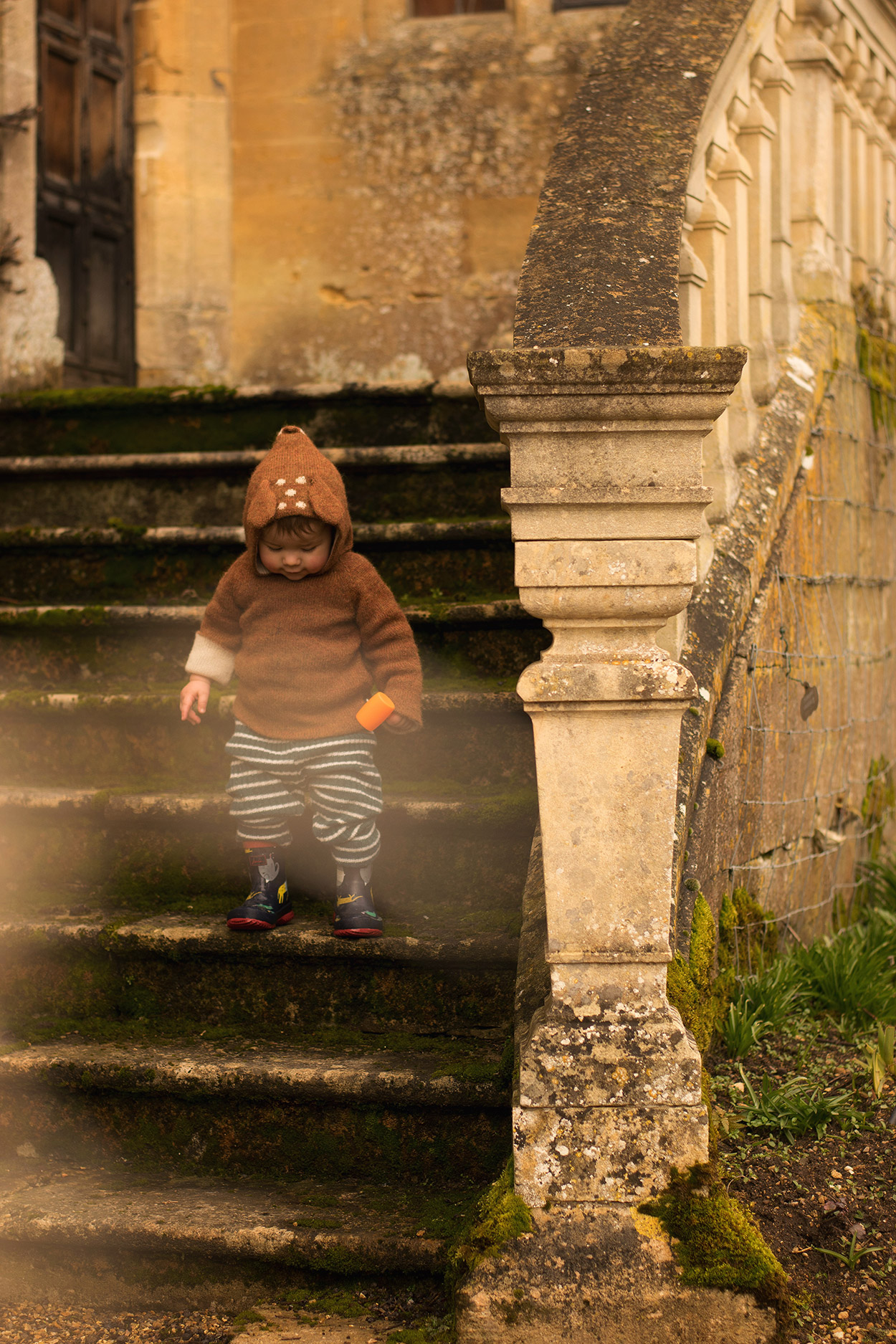 Young family visiting Sudeley Castle & Gardens, Cotswolds, Gloucestershire, with two young boys wearing Bobo Choses impossible glasses jumper and Oeuf Bambi knitted hoody and Joules wellies exploring the grounds in Spring