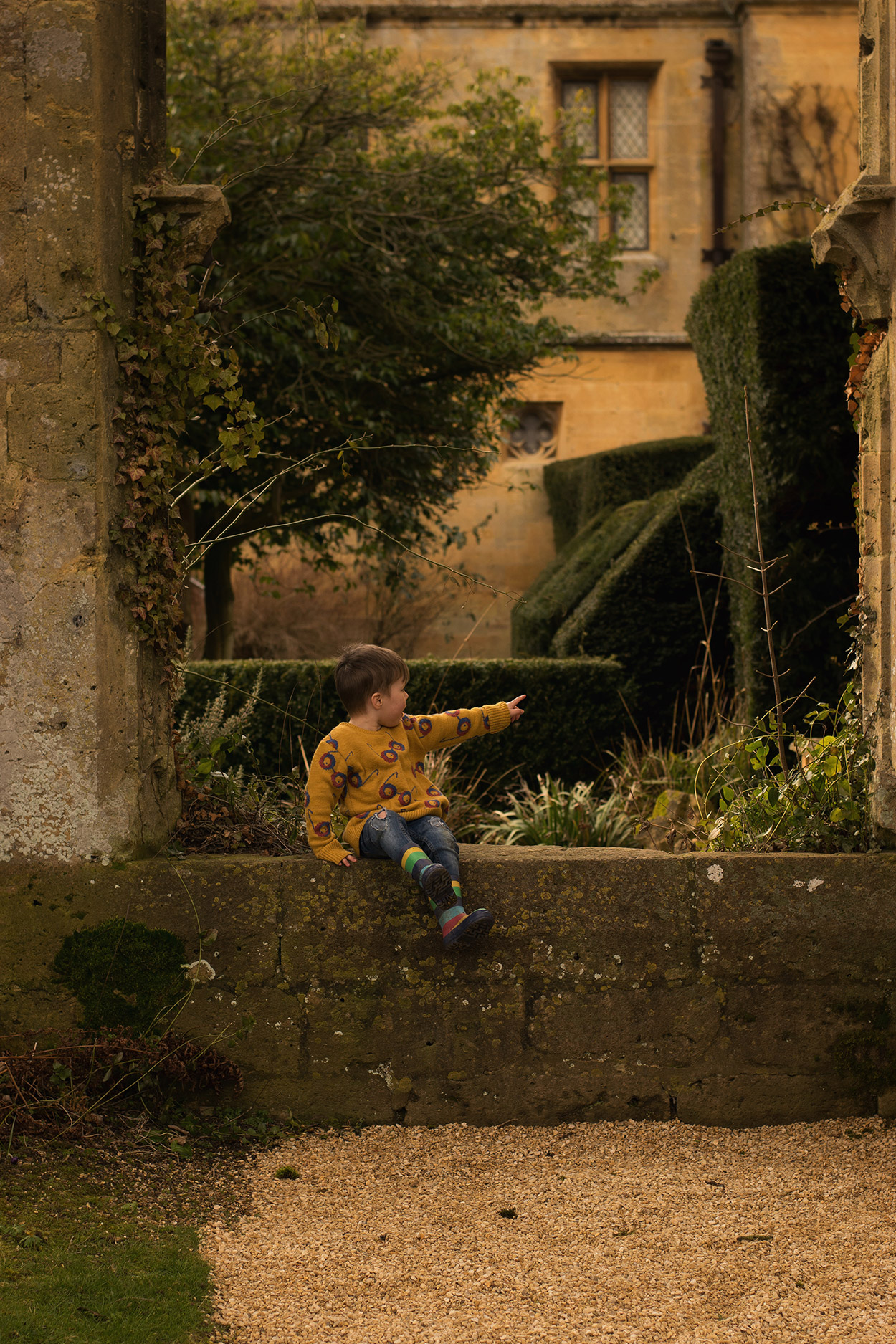 Young family visiting Sudeley Castle & Gardens, Cotswolds, Gloucestershire, with two young boys wearing Bobo Choses impossible glasses jumper and Oeuf Bambi knitted hoody and Joules and Frugi puddlebuster wellies exploring the grounds in Spring