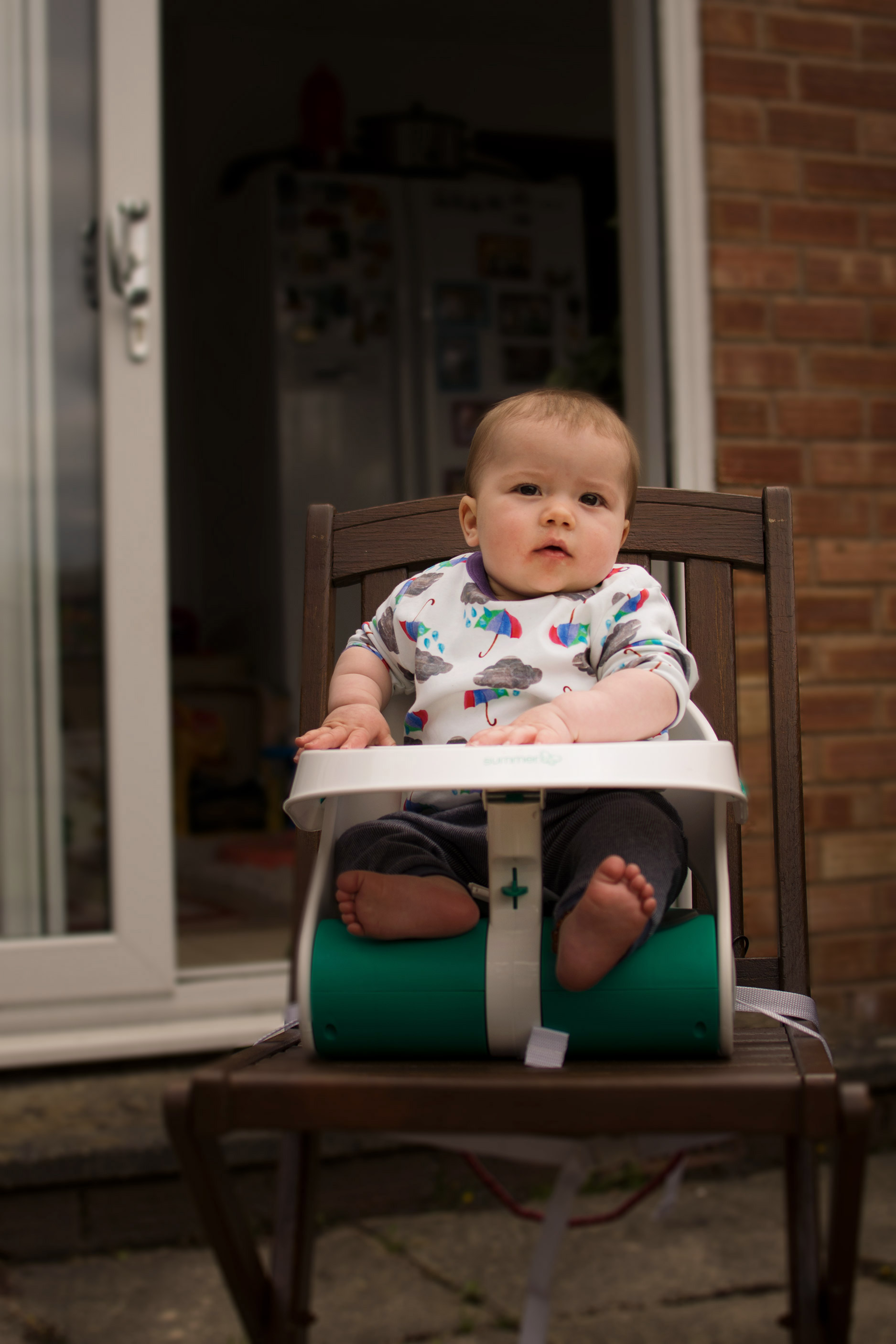 Review: Summer Travel Booster Seat - 9 month old baby boy sitting in his Summer portable highchair wearing rainy day t-shirt from the Bunting Tree in the garden