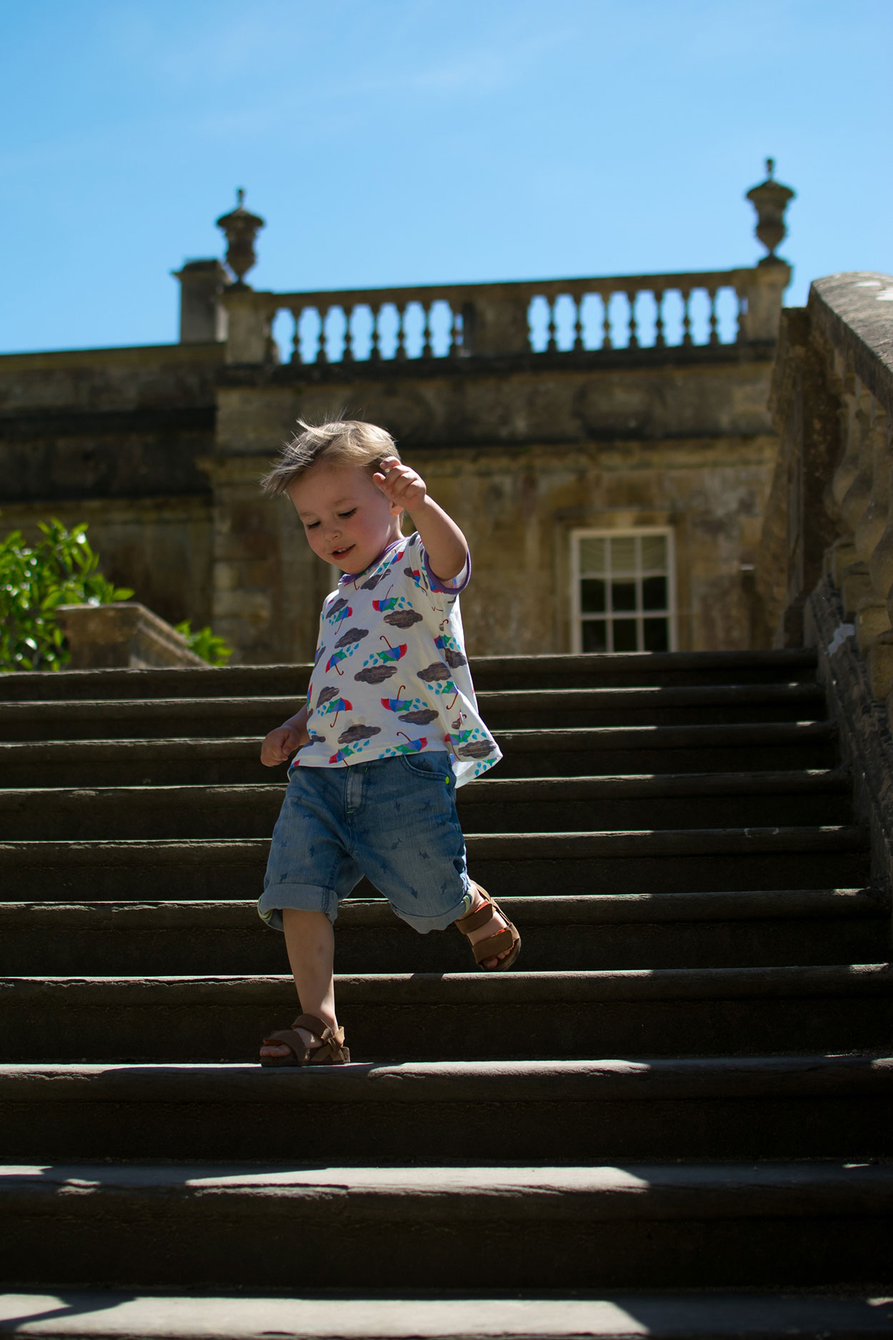 Of Wildlife and Water {To Adventure #2} - 3 year old wearing The Bunting Tree rainclouds and umbrellas t-shirt running down the stairs of the manor house at Dyrham Park, Bath
