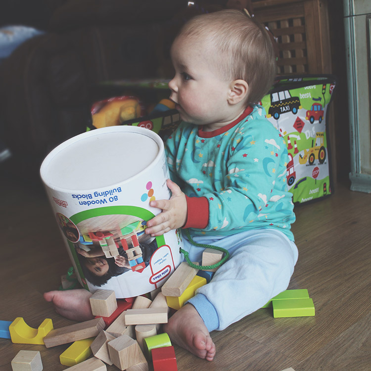 My Toddler Hates Me And I Know Why - Toddler pouring wooden building blocks on the floor