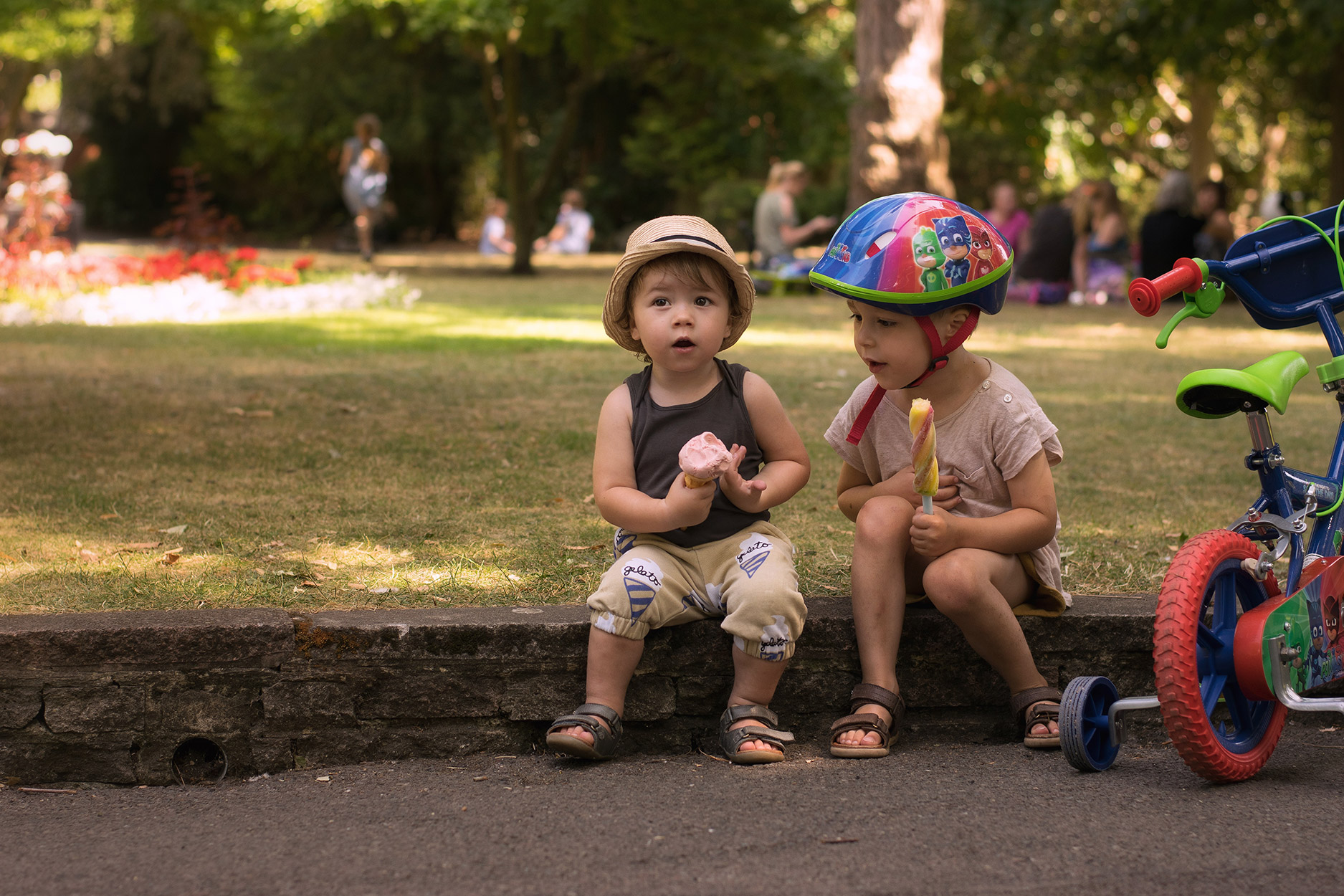 Pre-schooler learning to ride his PJ Masks bicycle on a Summers Day with brother wearing Le Petit Germain, Hugo Loves Tiki gelato shorts and trilby hat with Nanny