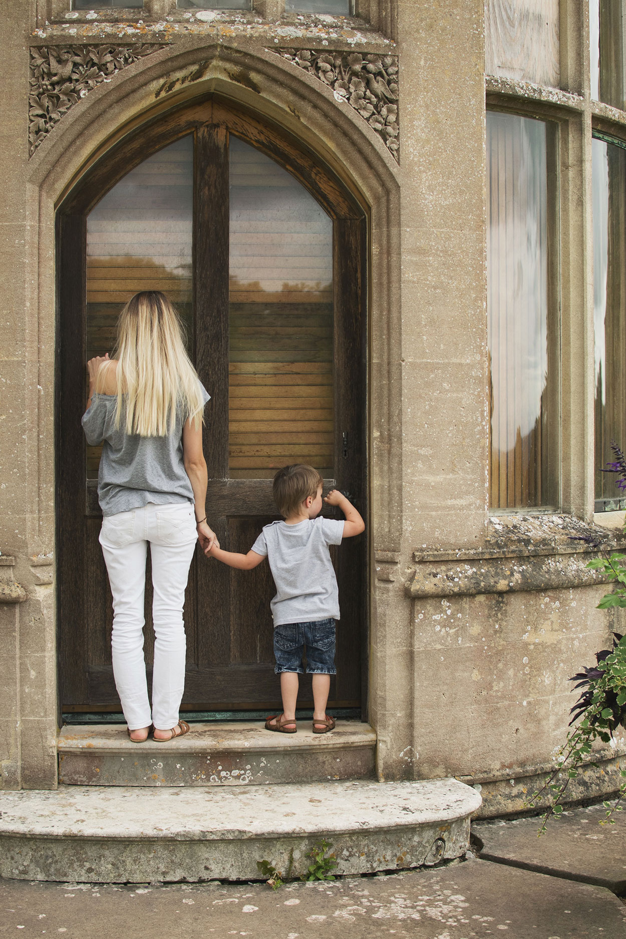 Mother and pre-school son wearing white jeans and Frugi rainbow t-shirt knocking on the door of the manor at at Tyntesfield Estate, Hampshire, National Trust