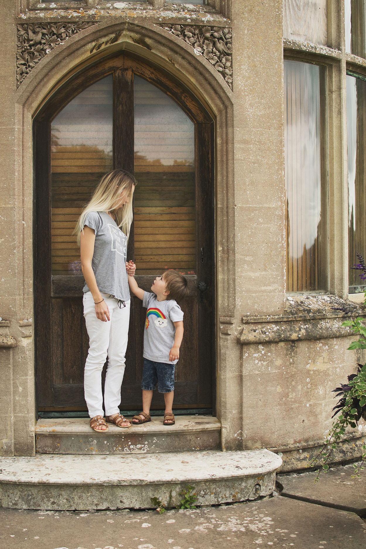 Mother and pre-school son wearing white jeans and Frugi rainbow t-shirt knocking on the door of the manor at Tyntesfield Estate, Hampshire, National Trust