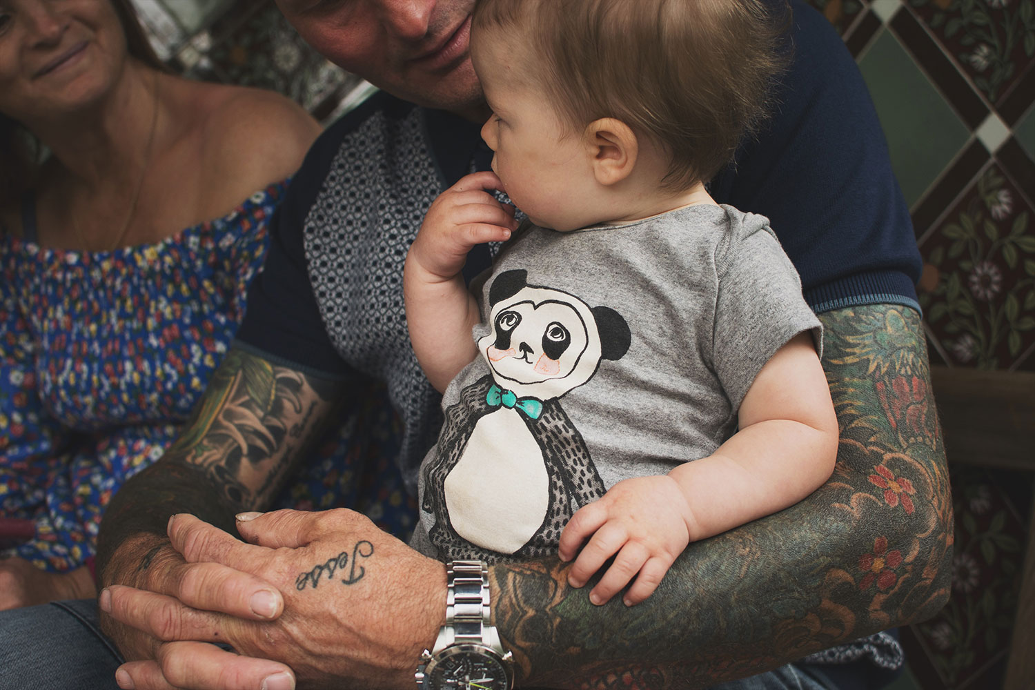 Grandparents with tattoos holding baby grandson wearing soft gallery panda romper in the rose garden at Tyntesfield Estate, Hampshire, National Trust