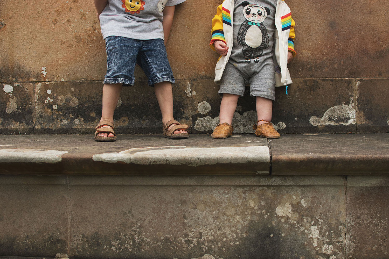 Two brothers wearing Frugi, Little Bird and Soft Gallery standing on the concrete bench at Tyntesfield Estate, Hampshire, National Trust