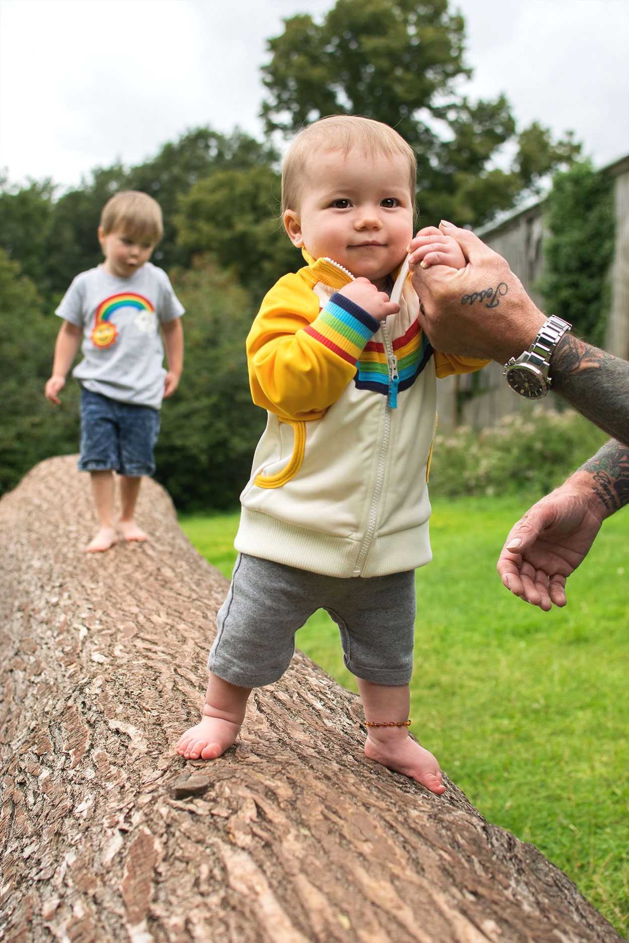 Young brothers wearing rainbow Frugi t-shirt and Little Bird vintage yellow jacket walking barefoot along the tree trunk at Tyntesfield Estate, Hampshire, National Trust