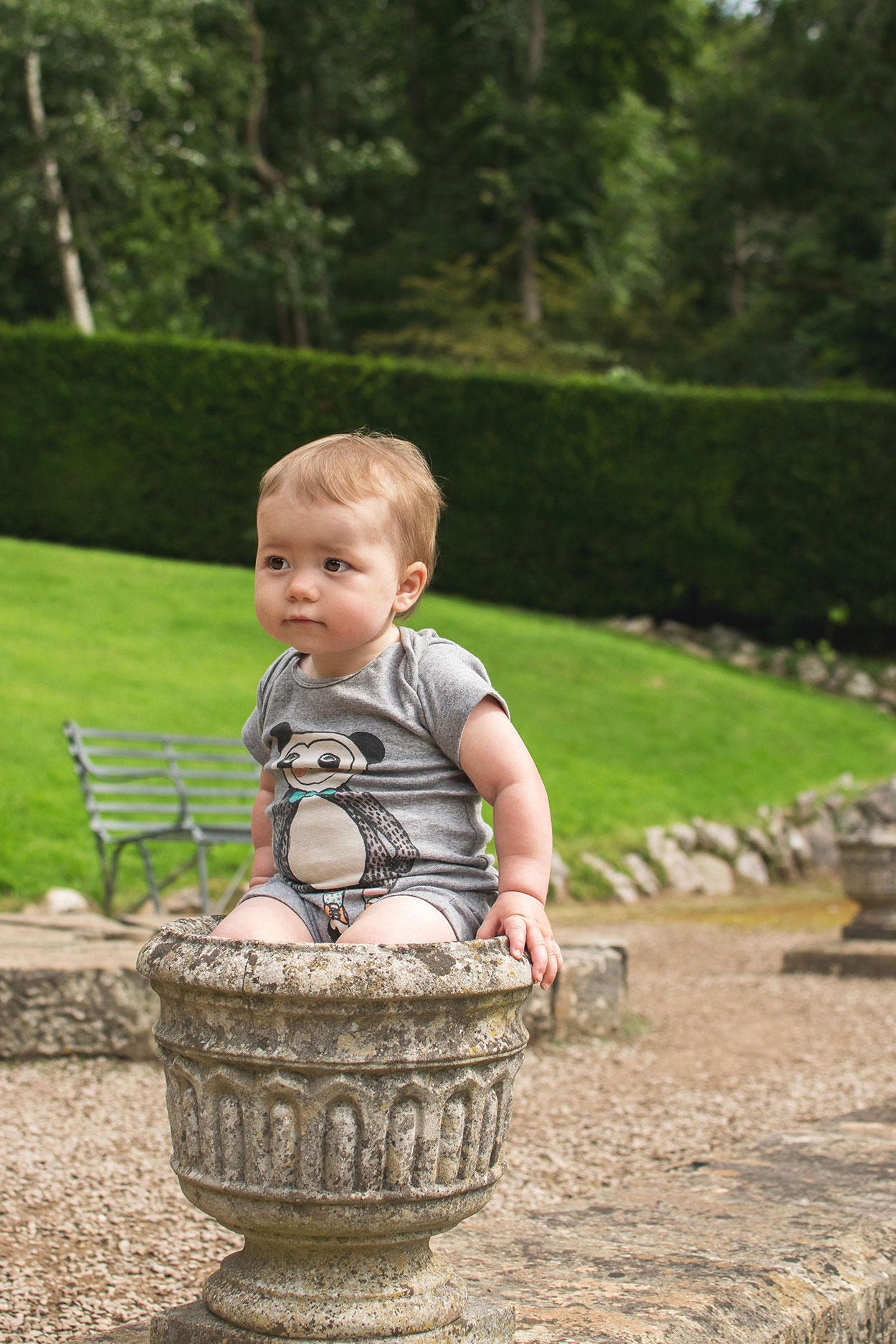 Baby boy wearing Soft Gallery panda romper sitting in one of the concrete vases on the stairs in the rose garden at Tyntesfield Estate, Hampshire, National Trust