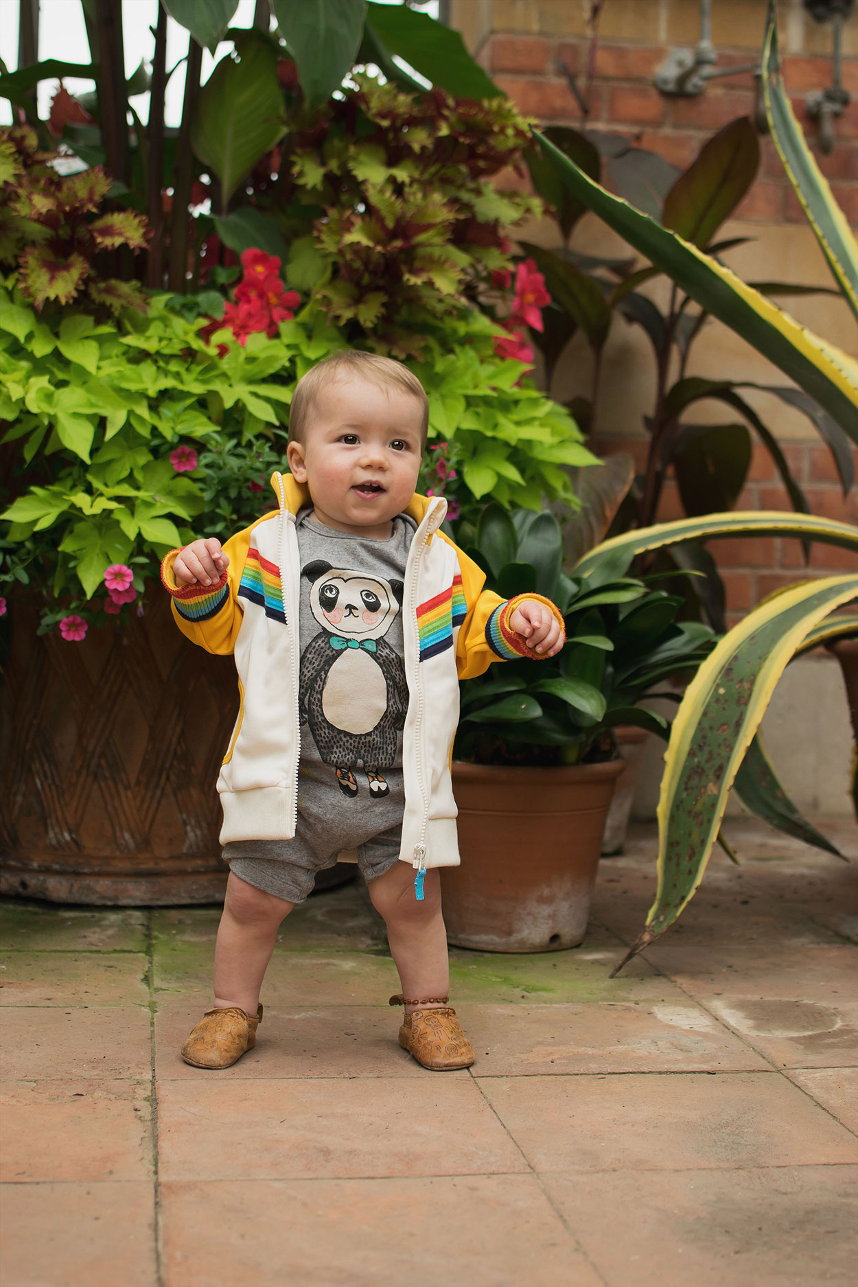 Young toddler boy wearing Soft Gallery panda romper, Little Bird vintage yellow rainbow jacket and Easy Peasy leather pirate shoes standing in the orangery at Tyntesfield Estate, Hampshire, National Trust
