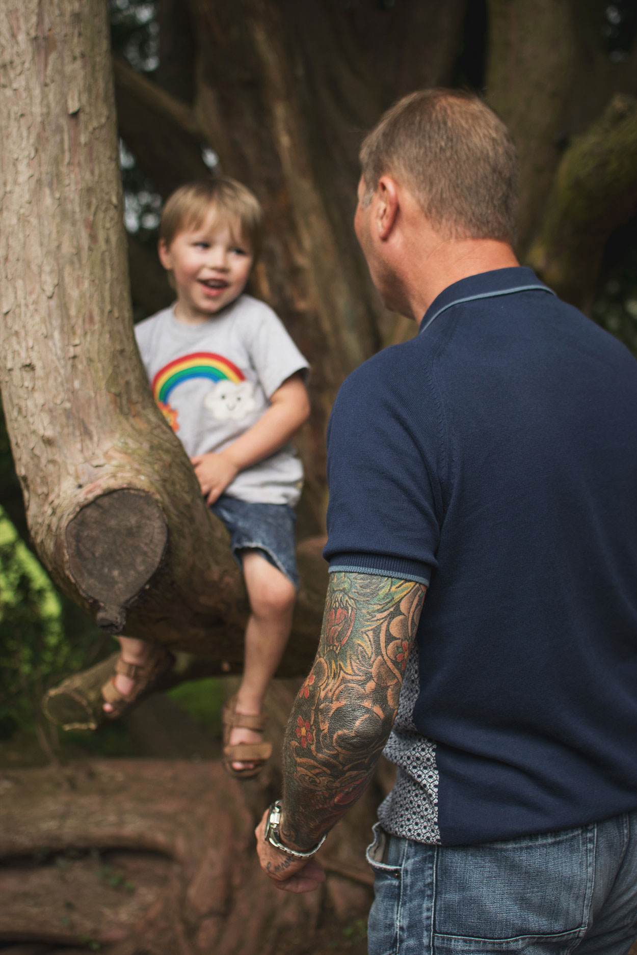 Tattooed Grandad with grandson climbing the trees at Tyntesfield Estate, Hampshire, National Trust