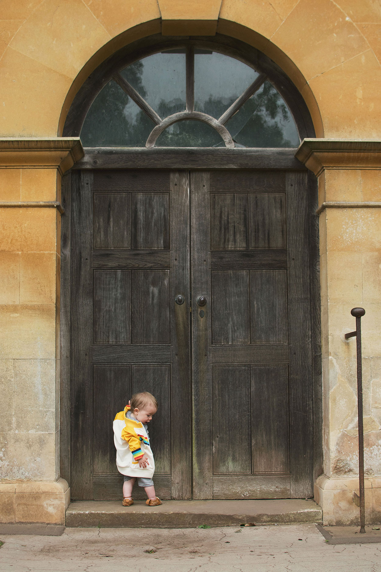 Young boy wearing Soft Gallery panda romper and Little Bird vintage yellow jacket looking at large door at Tyntesfield Estate, Hampshire, National Trust