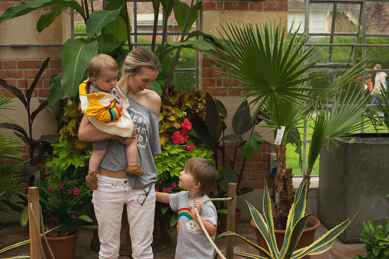 Mother and two sons standing in front of the plants of the orangery at Tyntesfield Estate, Hampshire, National Trust